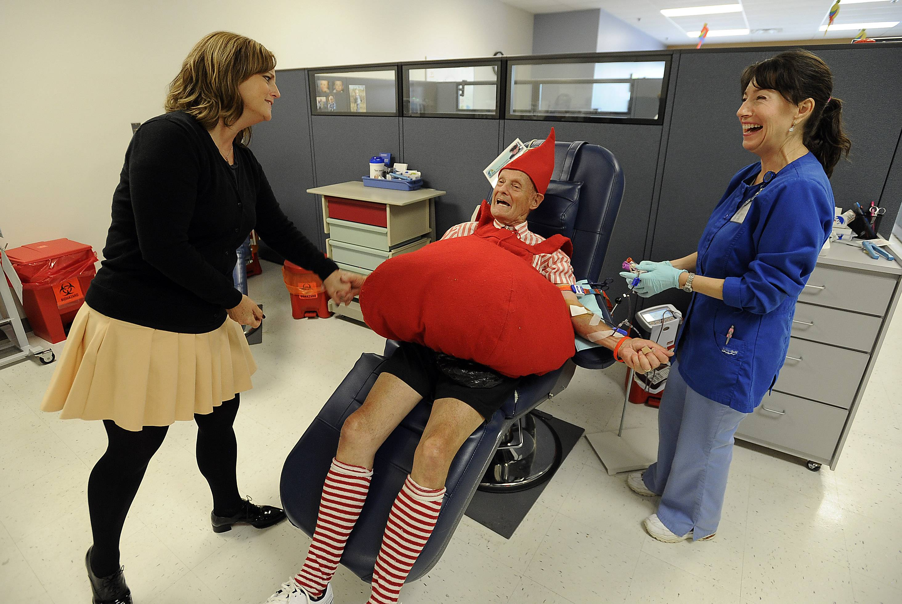 Palatine resident George Serena, 86, jokes with Geri Venable, director of donor services at LifeSource, left, and phlebotomist Jennifer Sava while donating his 151st pint of blood at LifeSource in Arlington Heights on Tuesday.