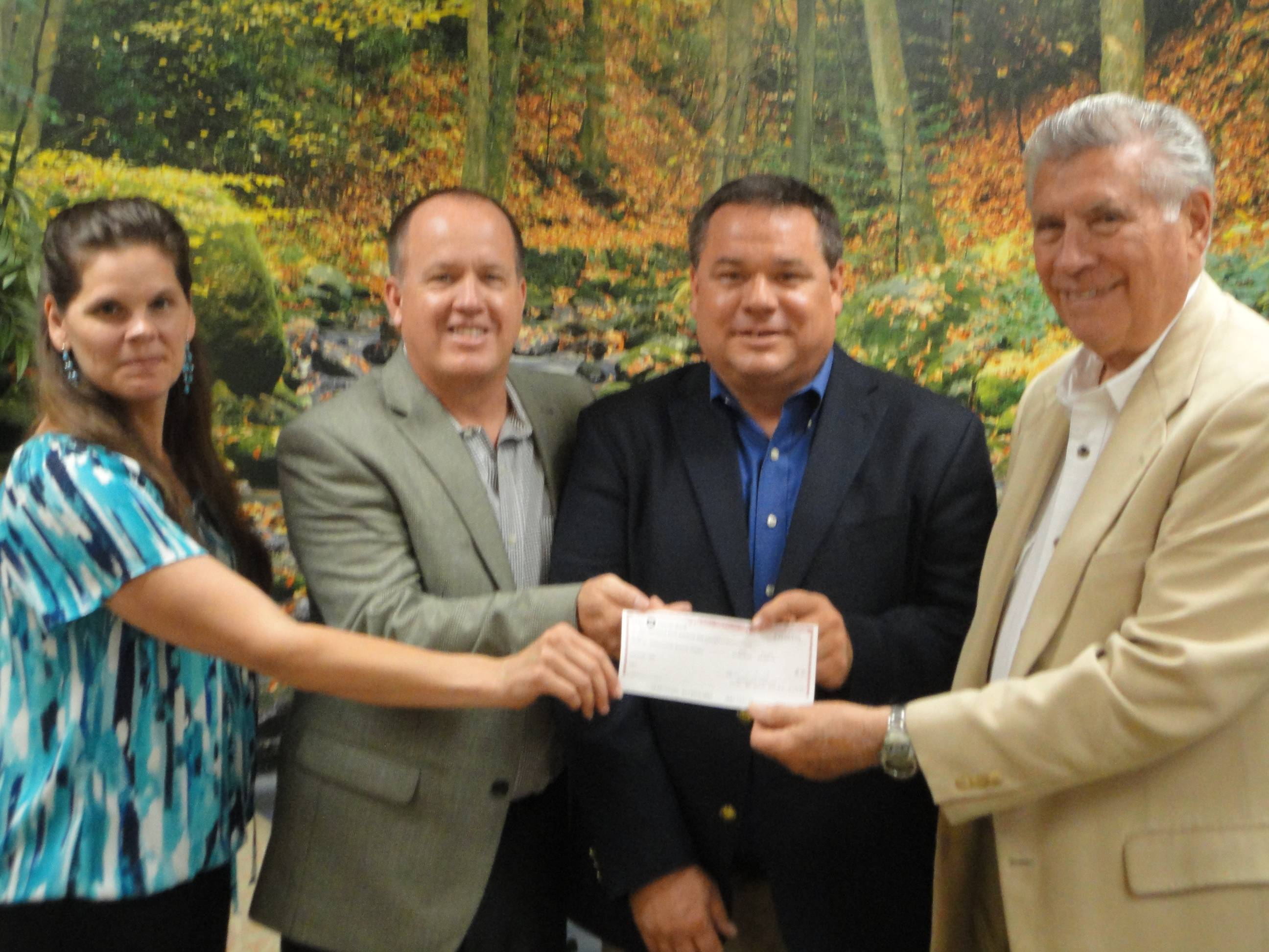 Kristin Maxwell, left, and Floyd Kettering, right, of Humanitarian Service Project receive the donation for UPS representatives Todd Westberg, second from left, and Jim Slanker.
