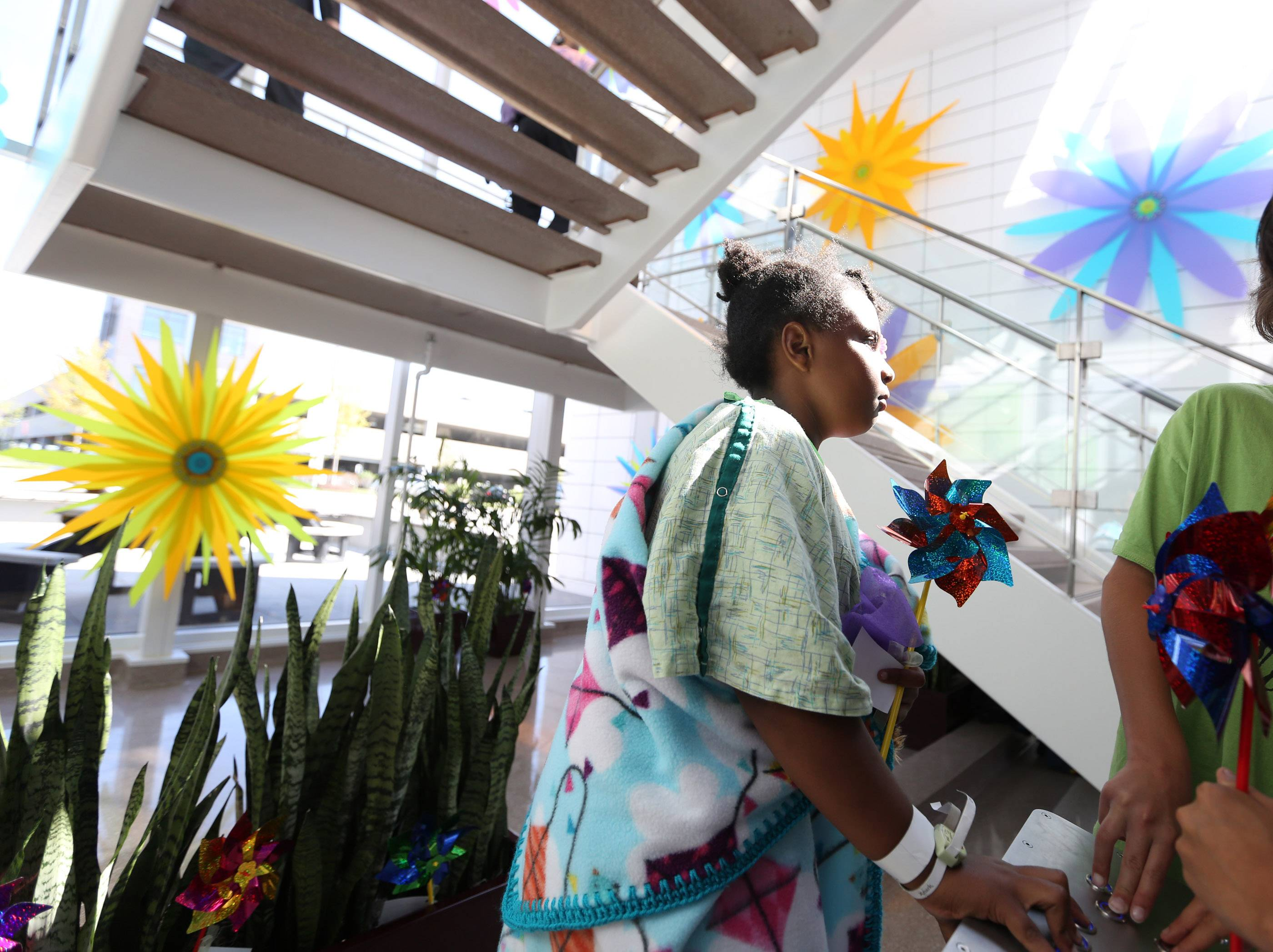 "Gabrielle Wesley, 8, left, pushes buttons that make flowers spin at an unveiling celebration of ""Bloom"" at Alexian Brothers Women and Children's Hospital in Hoffman Estates."