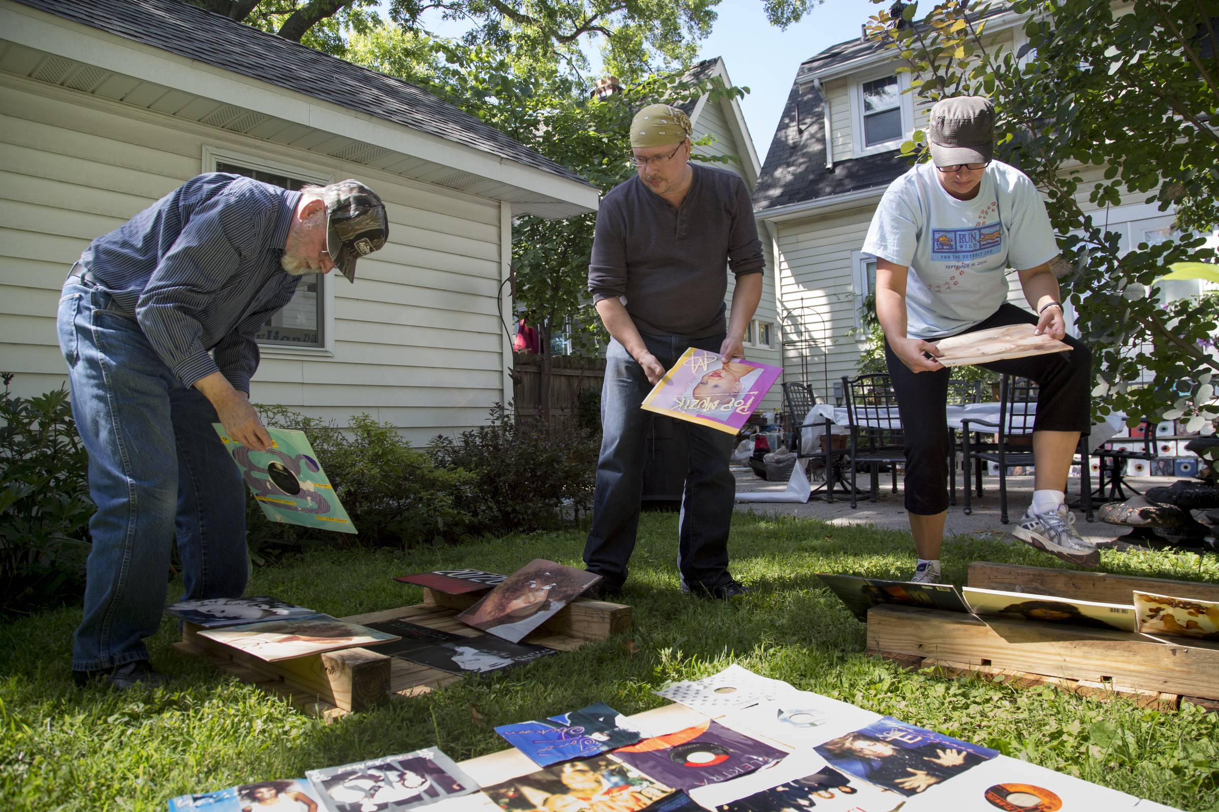 From left, Joe Pawlica, 80, of Warren, helps his son City councilman Greg Pawlica, 46, of Ferndale, go through his soaked album collection with neighbor Wanda Korgol, 41 of Ferndale, after water rose over a foot in his basement.