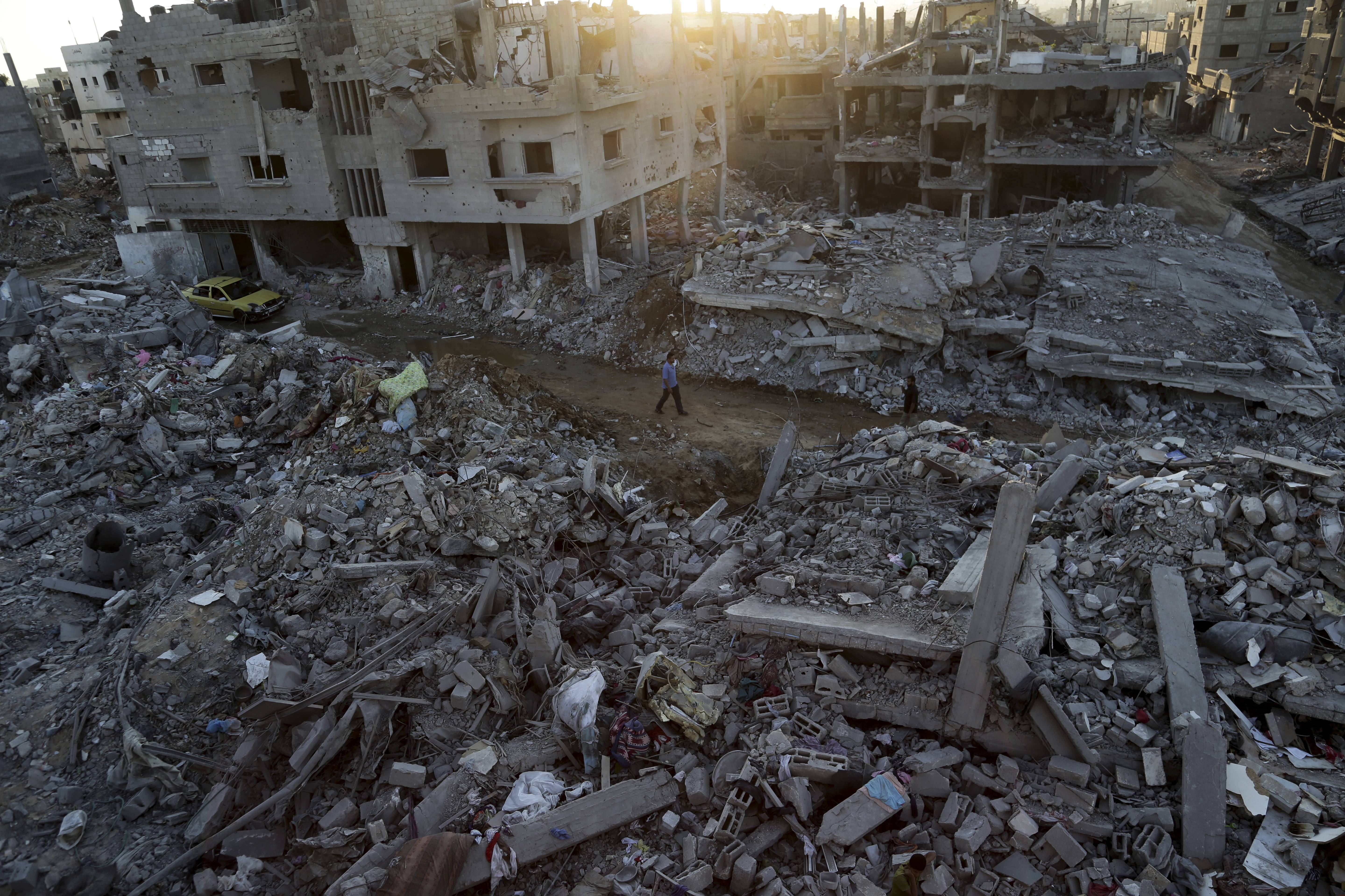 Palestinians walks next the rubble of homes destroyed by Israeli strikes in the town of Beit Hanoun, in the northern Gaza Strip, Tuesday, Aug. 12, 2014.