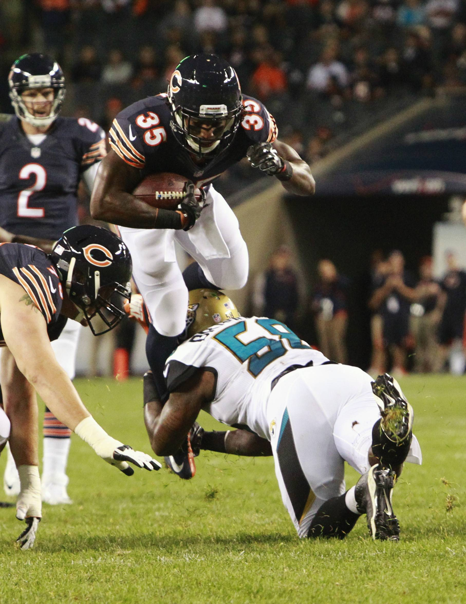 Bears running back Senorise Perry (35) tries to leap over Jacksonville Jaguars defensive end Allen Bradford (58) during the second half of the preseason football game in Chicago Thursday.