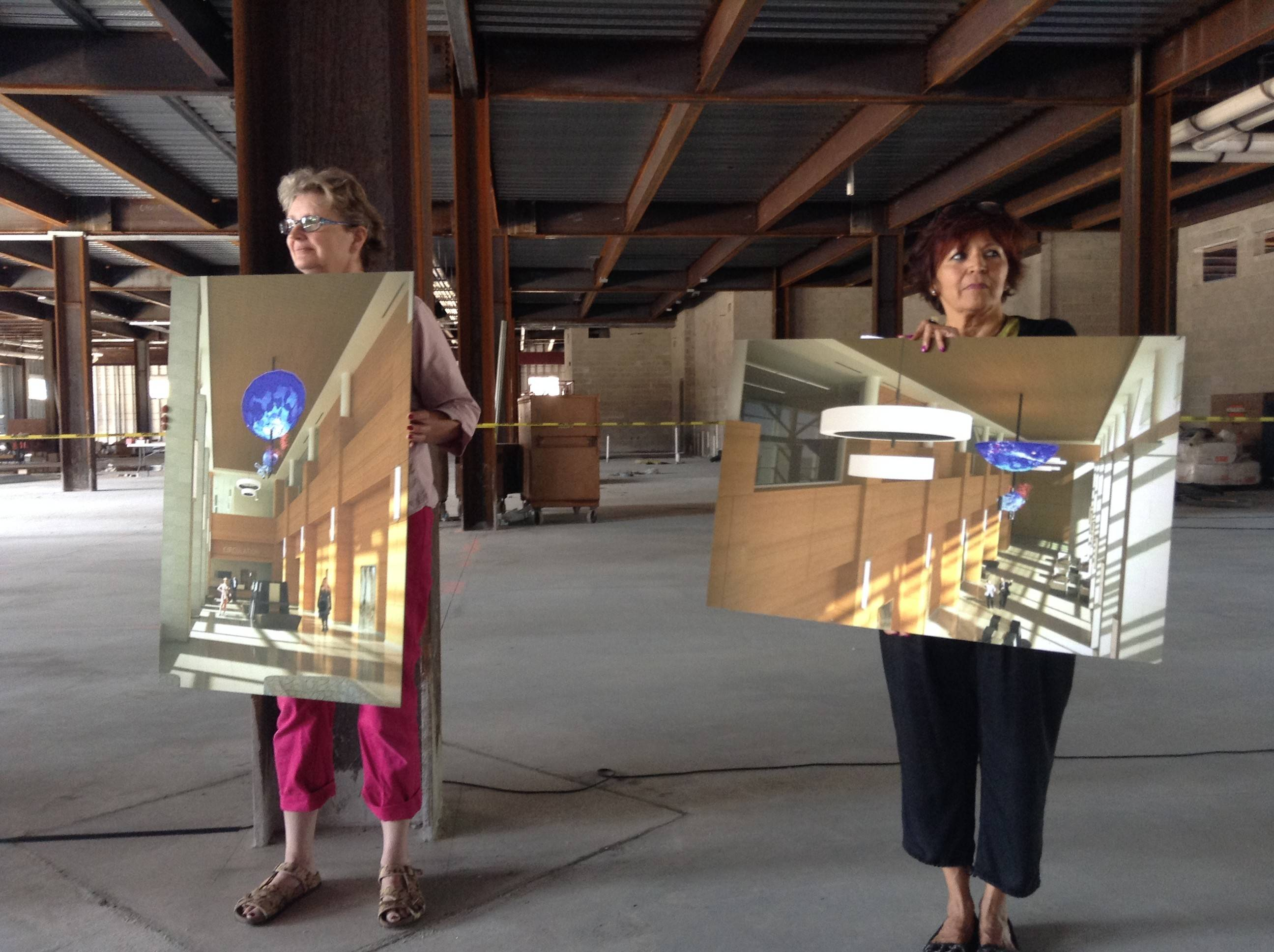 Aurora Public Library Foundation board members Ree Kline and Dee Basile showed community members Thursday of what will soon become of the concrete and steel shell behind them.