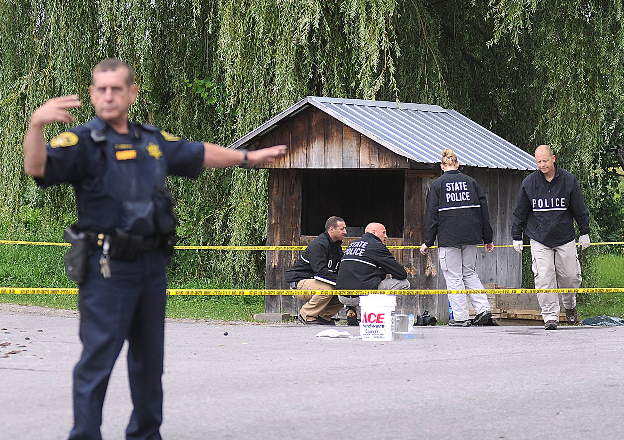 New York State Police crime scene investigators search for clues Thursday at a roadside vegetable stand in Oswegatchie, N.Y.
