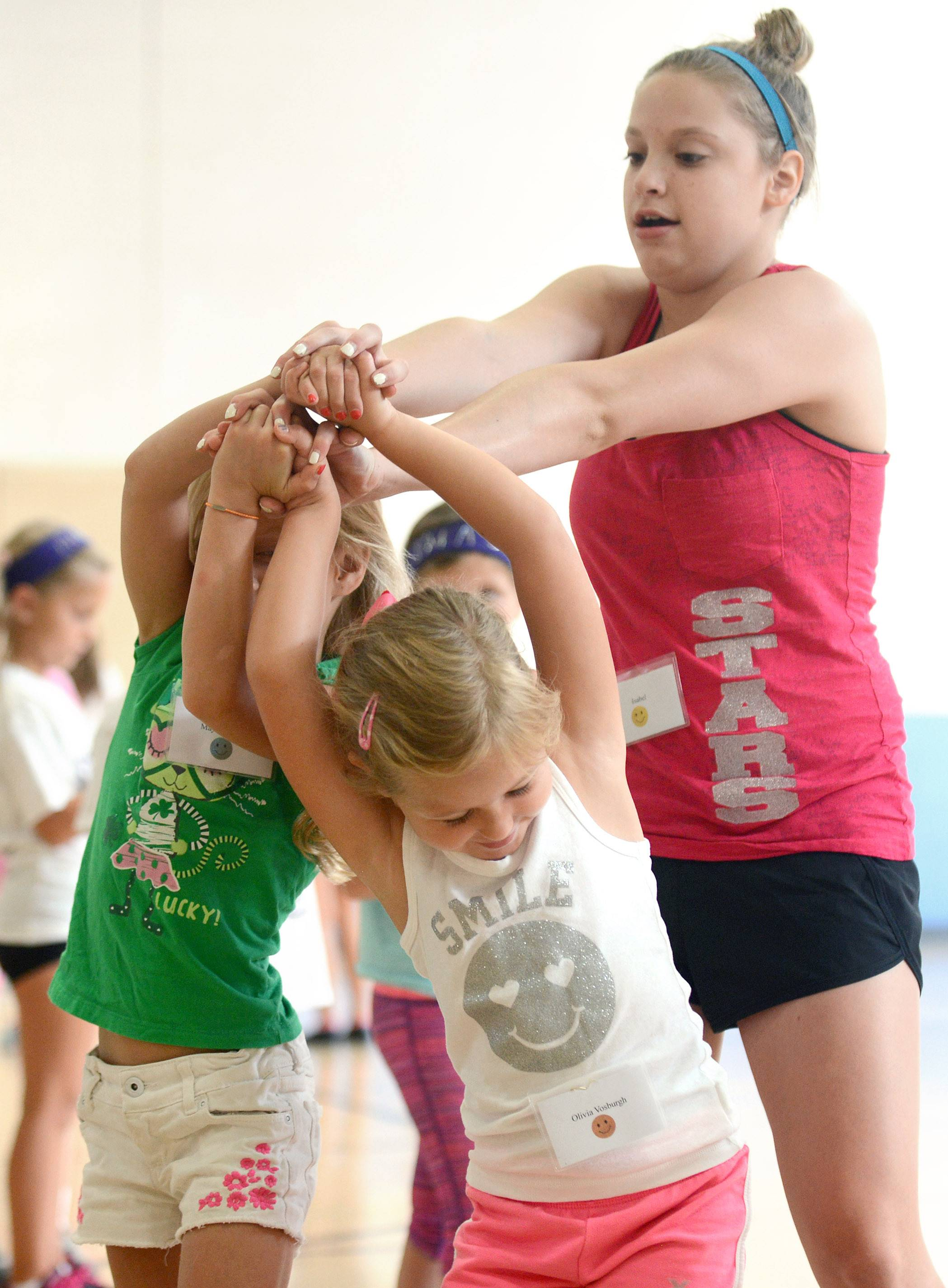 St. Charles North High School senior Isabel Miller, 17, helps Maya Mullally, left, and Olivia Vosburgh, both 6, with a joined-hands turn during the dance and drill teams' 15th annual dance clinic for elementary and middle school students Thursday at Bell-Graham Elementary School in St. Charles.