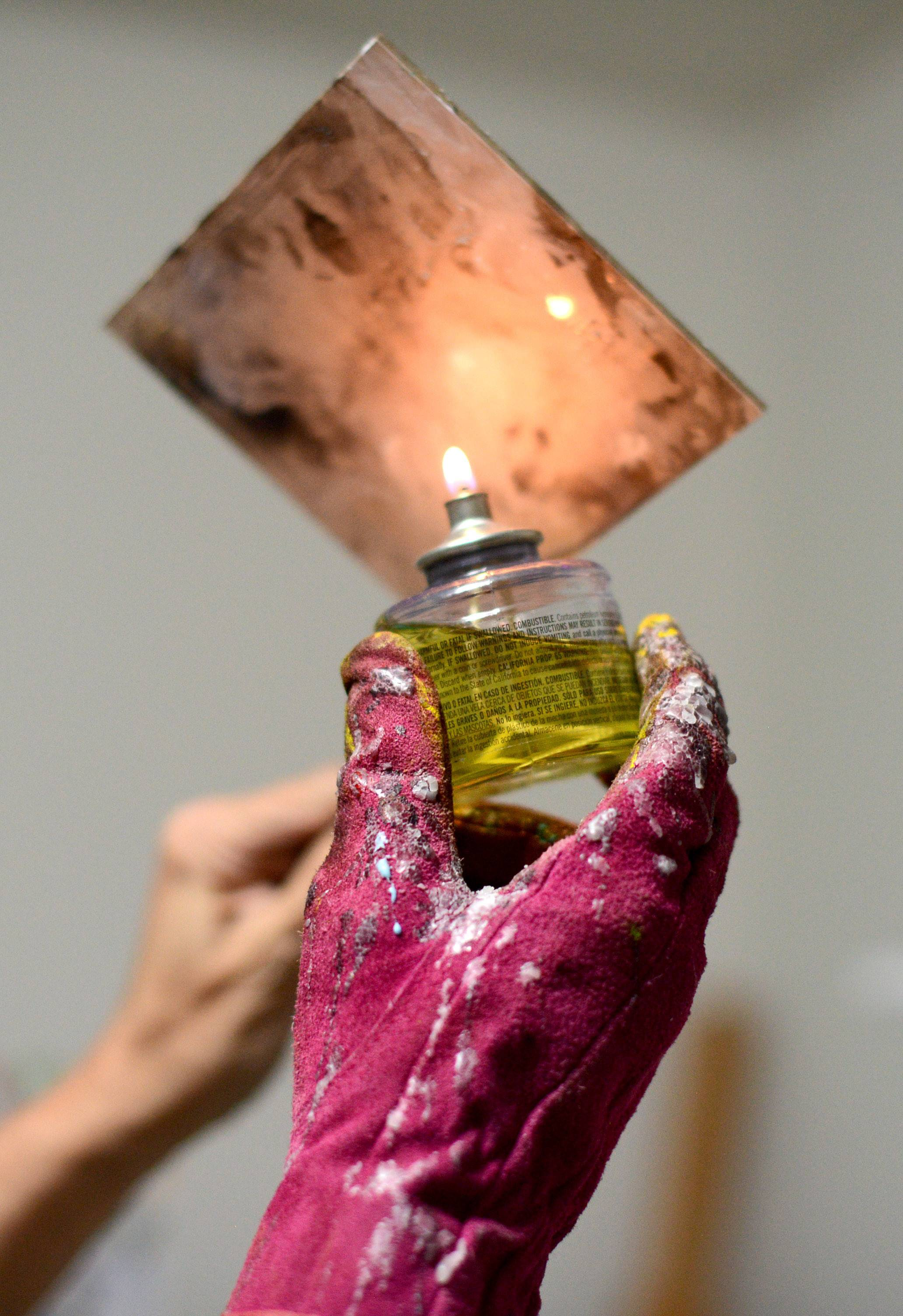 A tiki candle is applied to a tile canvas. Anne Ressman Zabinski uses a glove to protect her hand from flame and dripping wax when using a wax candle.