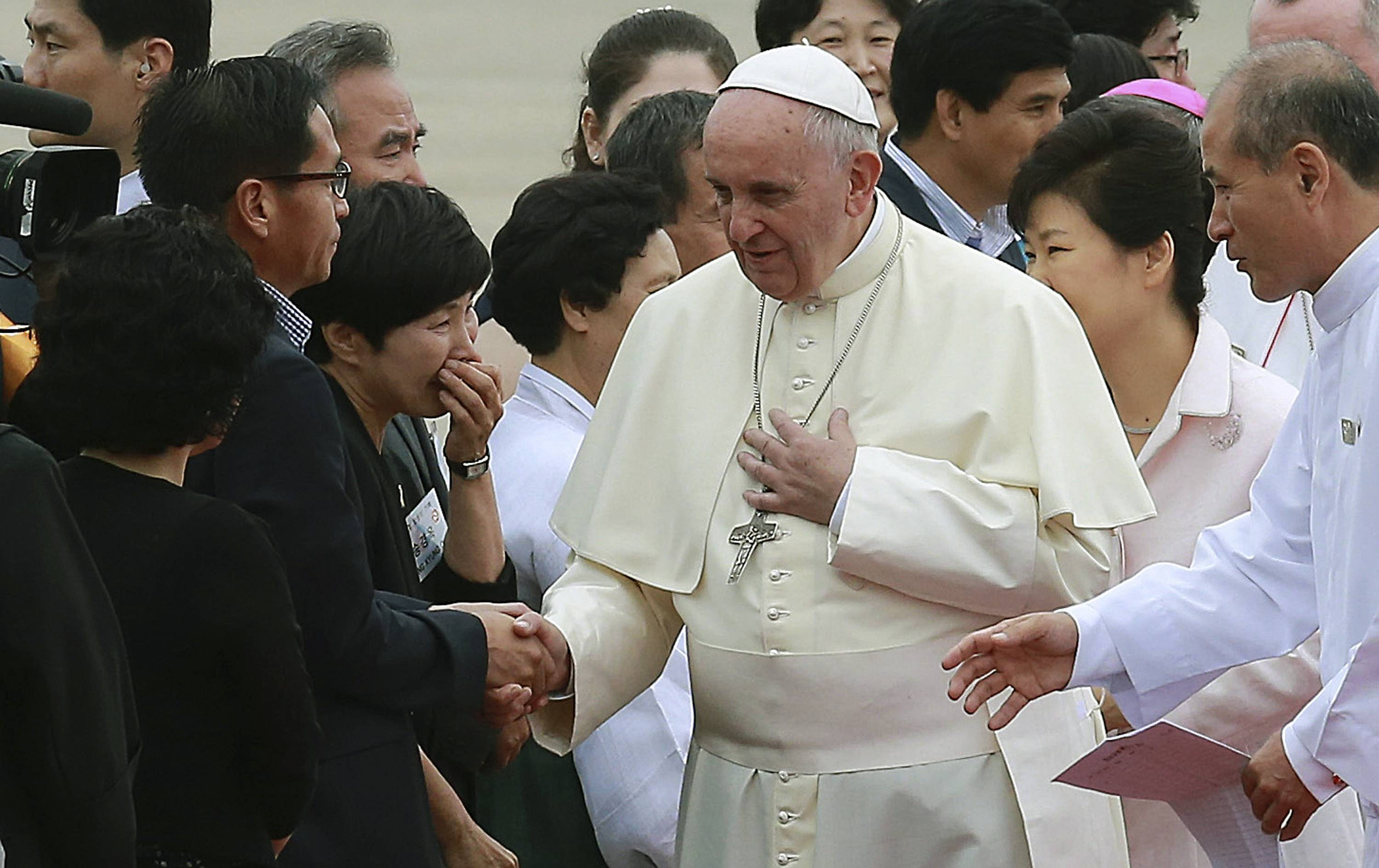 Pope Francis, center, shakes hands with a representatives of family members of victims onboard the sunken ferry Sewol upon his arrival at Seoul Air Base in Seongnam, South Korea, Thursday, Aug. 14, 2014.