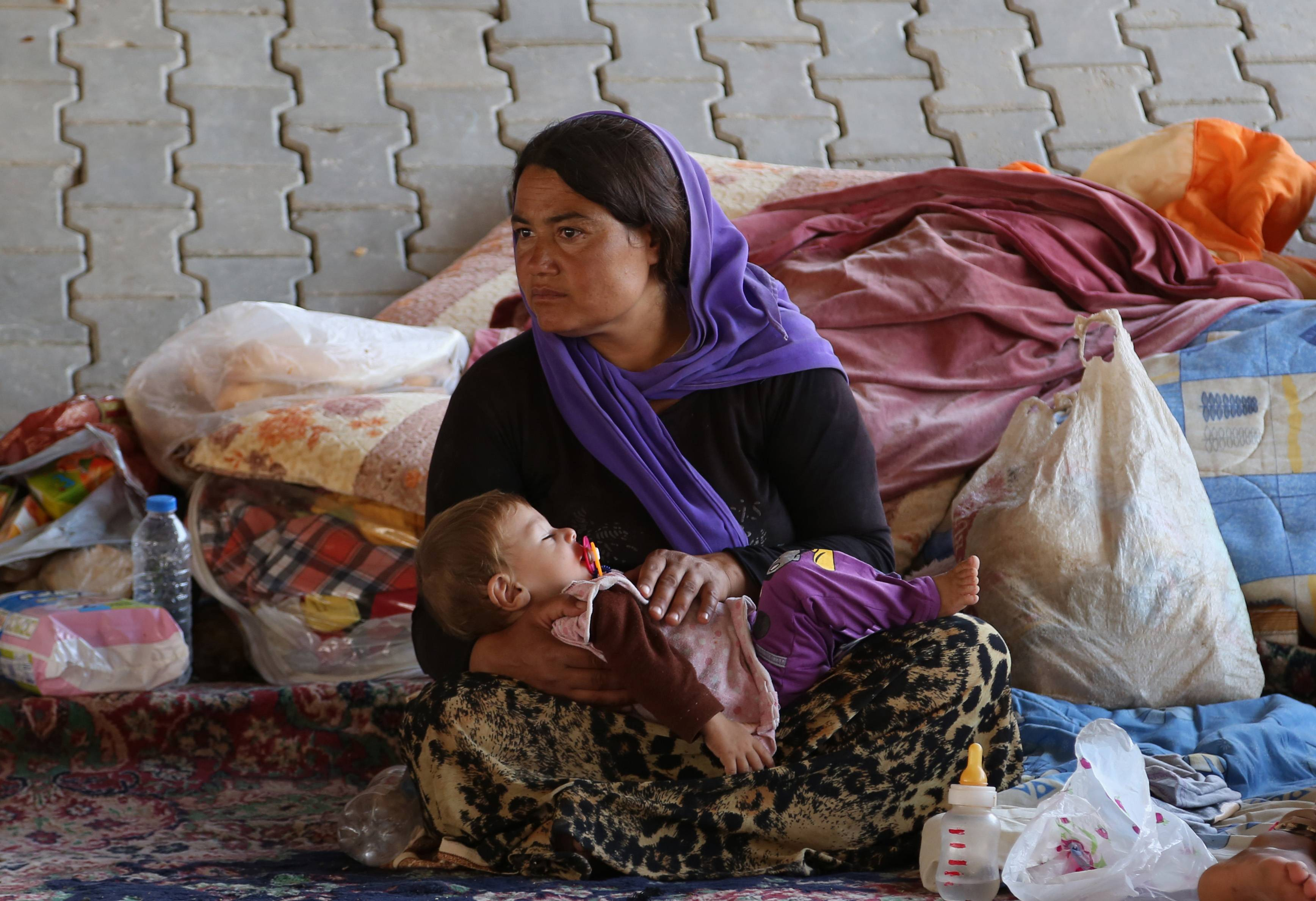 An Iraqi woman and her daughter from the Yazidi community settle under a bridge in Dahuk, 260 miles (430 kilometers) northwest of Baghdad, Iraq, Thursday, Aug. 14, 2014.