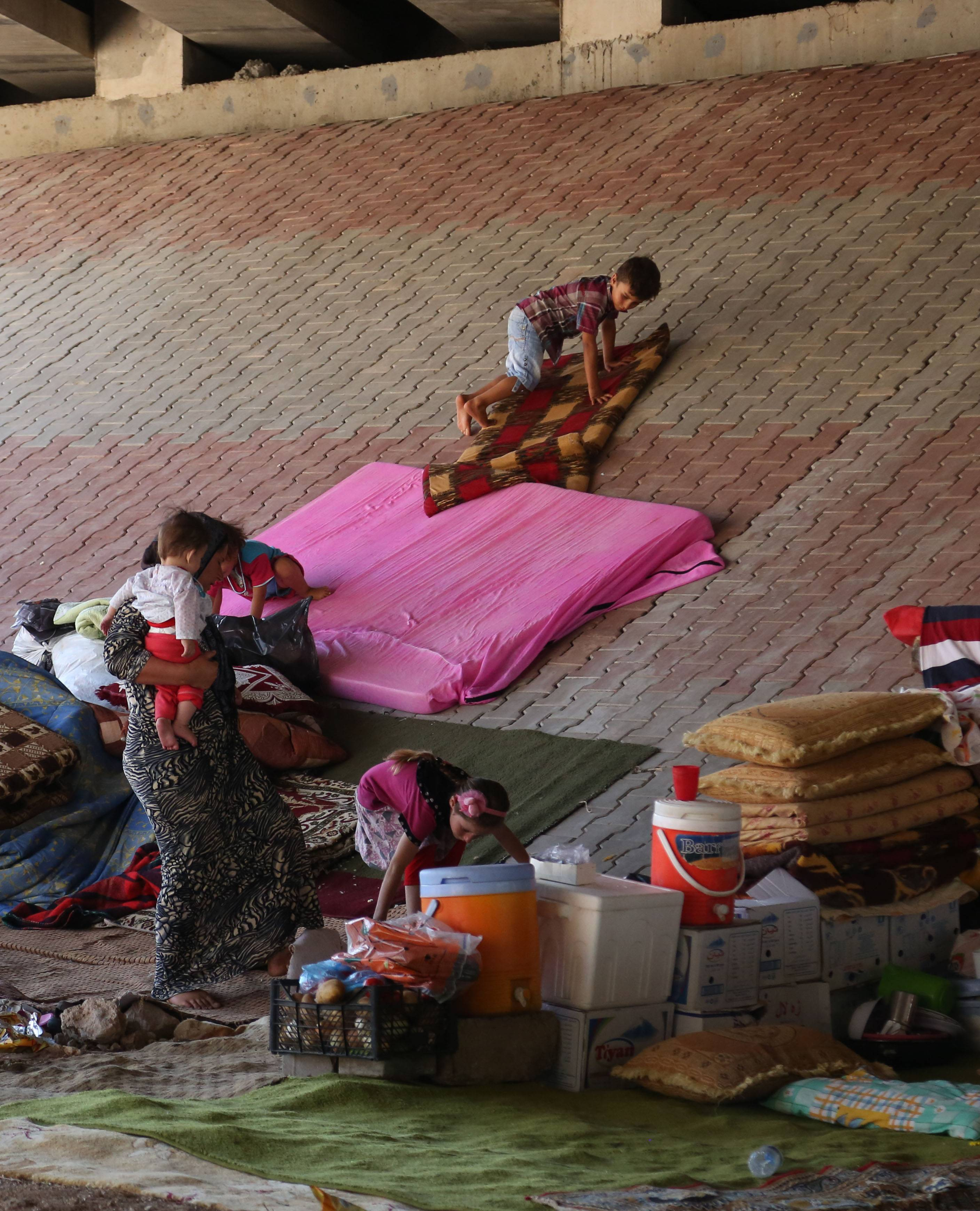 Displaced Iraqis from the Yazidi community settle under a bridge in Dahuk, 260 miles (430 kilometers) northwest of Baghdad, Iraq, Thursday, Aug. 14, 2014.