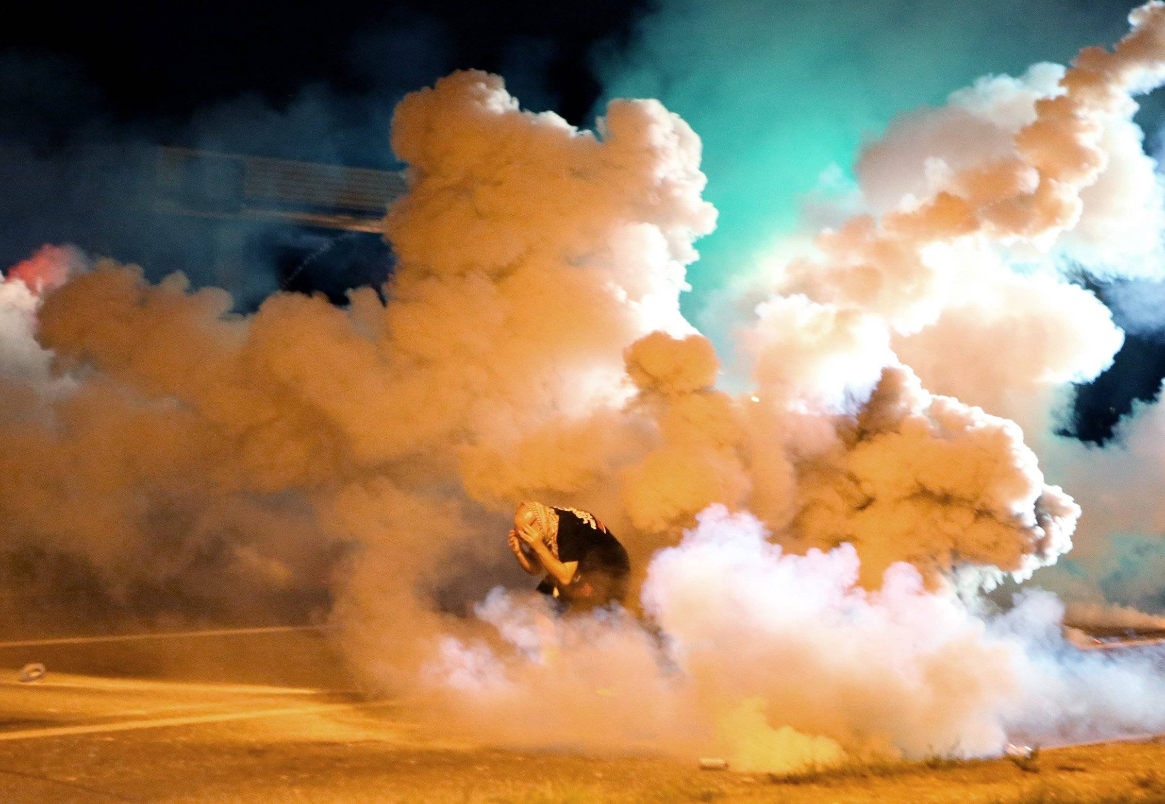 A protester takes shelter from smoke billowing around him Wednesday, Aug. 13, 2014, in Freguson, Mo.