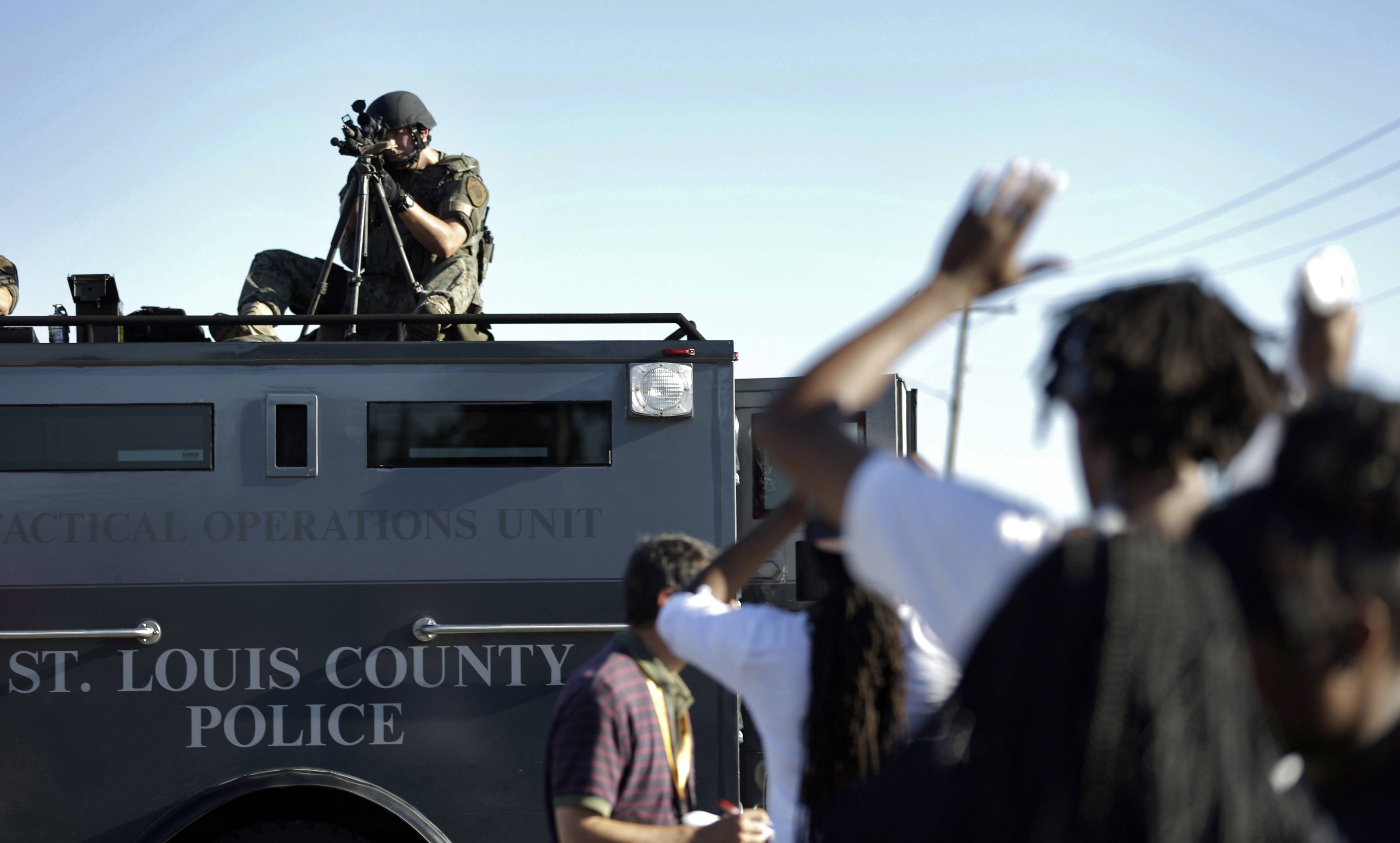 A member of the St. Louis County Police Department points his weapon in the direction of a group of protesters in Ferguson, Mo. on Wednesday, Aug. 13, 2014.