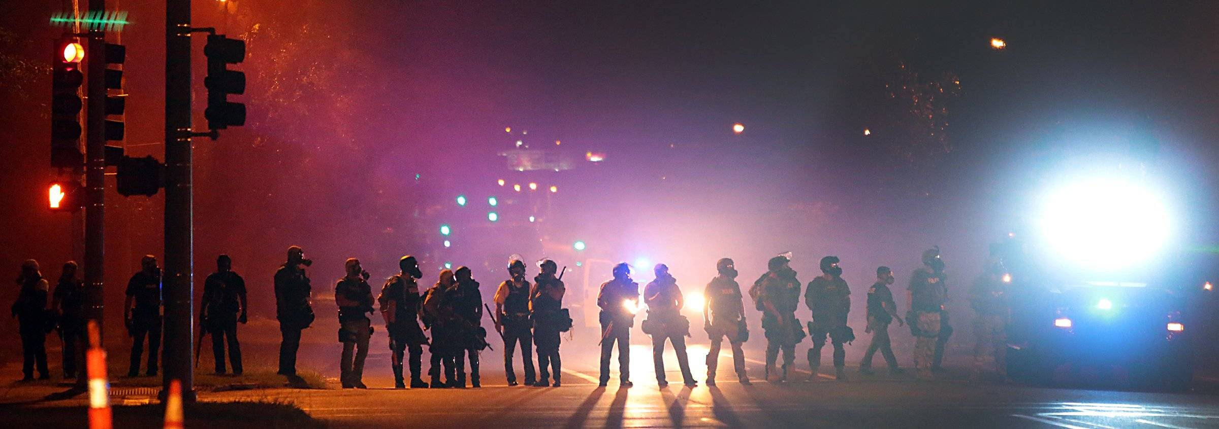 Police officers work their way north on West Florissant Avenue in Ferguson, Mo., clearing the road of people Wednesday, Aug. 13, 2014. Protests in the St. Louis suburb rocked by racial unrest since a white police officer shot an unarmed black teenager to death turned violent Wednesday night.