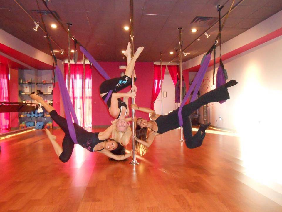 Studio owners Sarah Ritzman, center, and Caroline Patel, left, join instructor Alicia Svarkonis-Saso in a scene at Tiger Lily Vertical Fitness & Dance in Geneva that expands the concept of pole dancing.