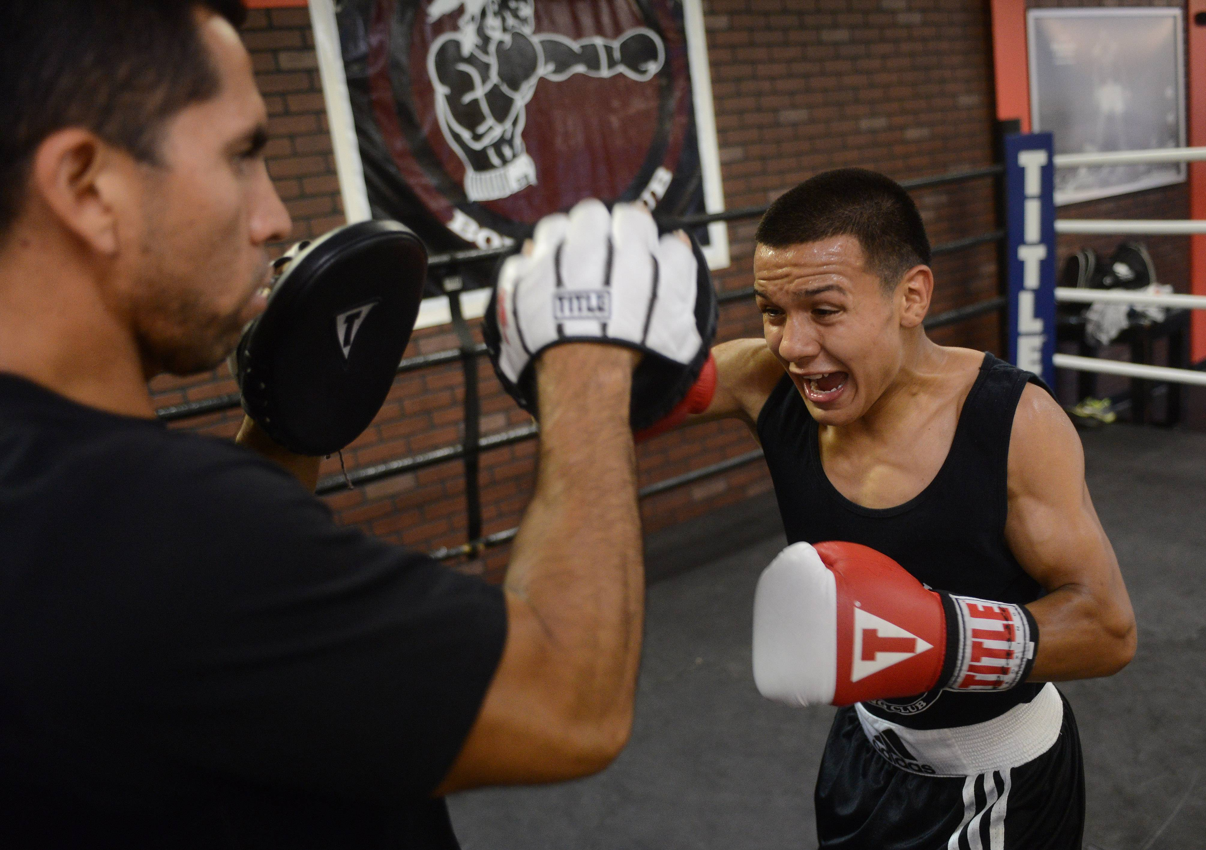 Boxer Javier Rivera, 19, works out with his coach, Pedro Calla, at Rumi Maki Boxing and Fitness gym in Palatine.