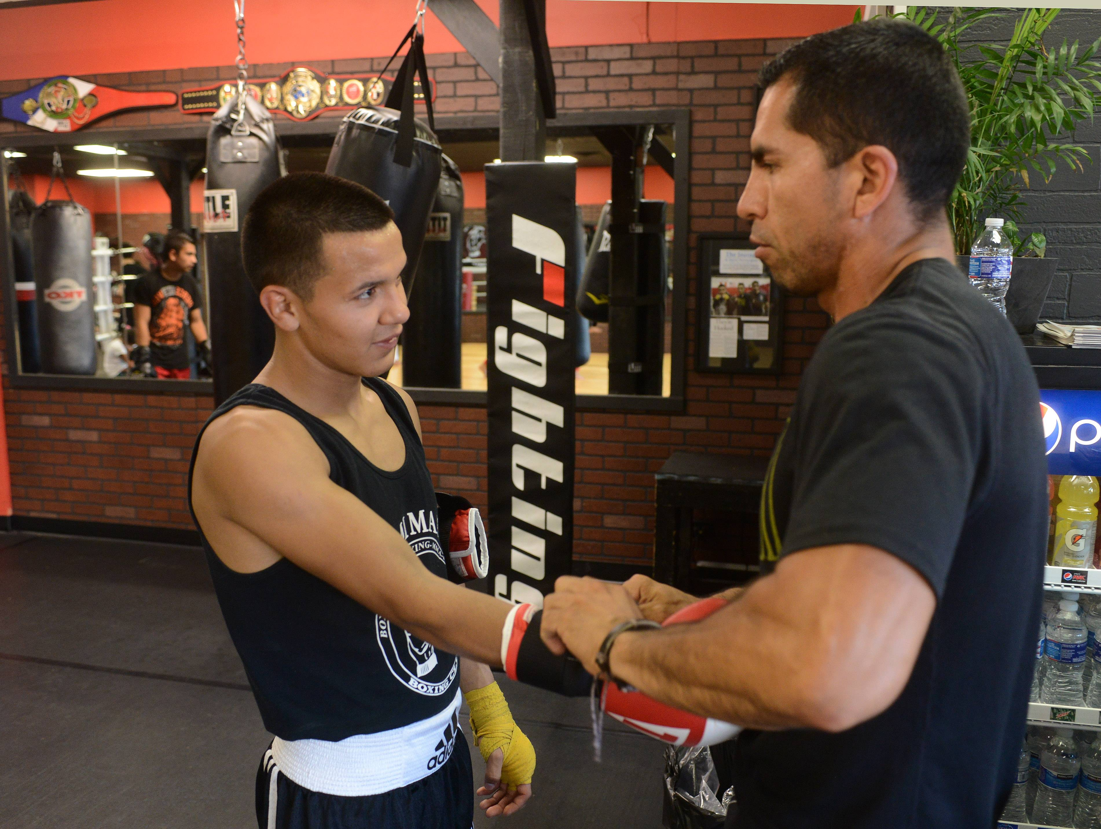 Getting involved in wrestling and later boxing helped him stay out of trouble, said Javier Rivera, 19. Here he's pictured with his coach, Pedro Calla, at Rumi Maki Boxing and Fitness Club in Palatine.