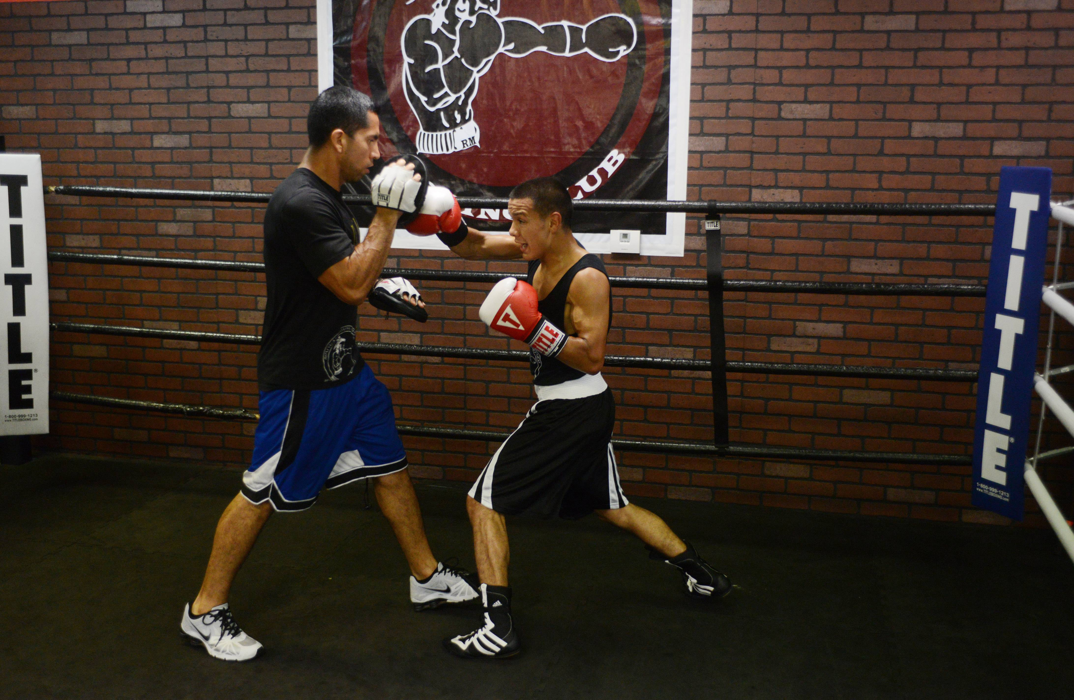 Javier Rivera, 19, works out with his coach, Pedro Calla, at Rumi Maki Boxing and Fitness Club in Palatine. Javier, a Palatine resident, credits his parents with teaching him to follow the right path while growing up.