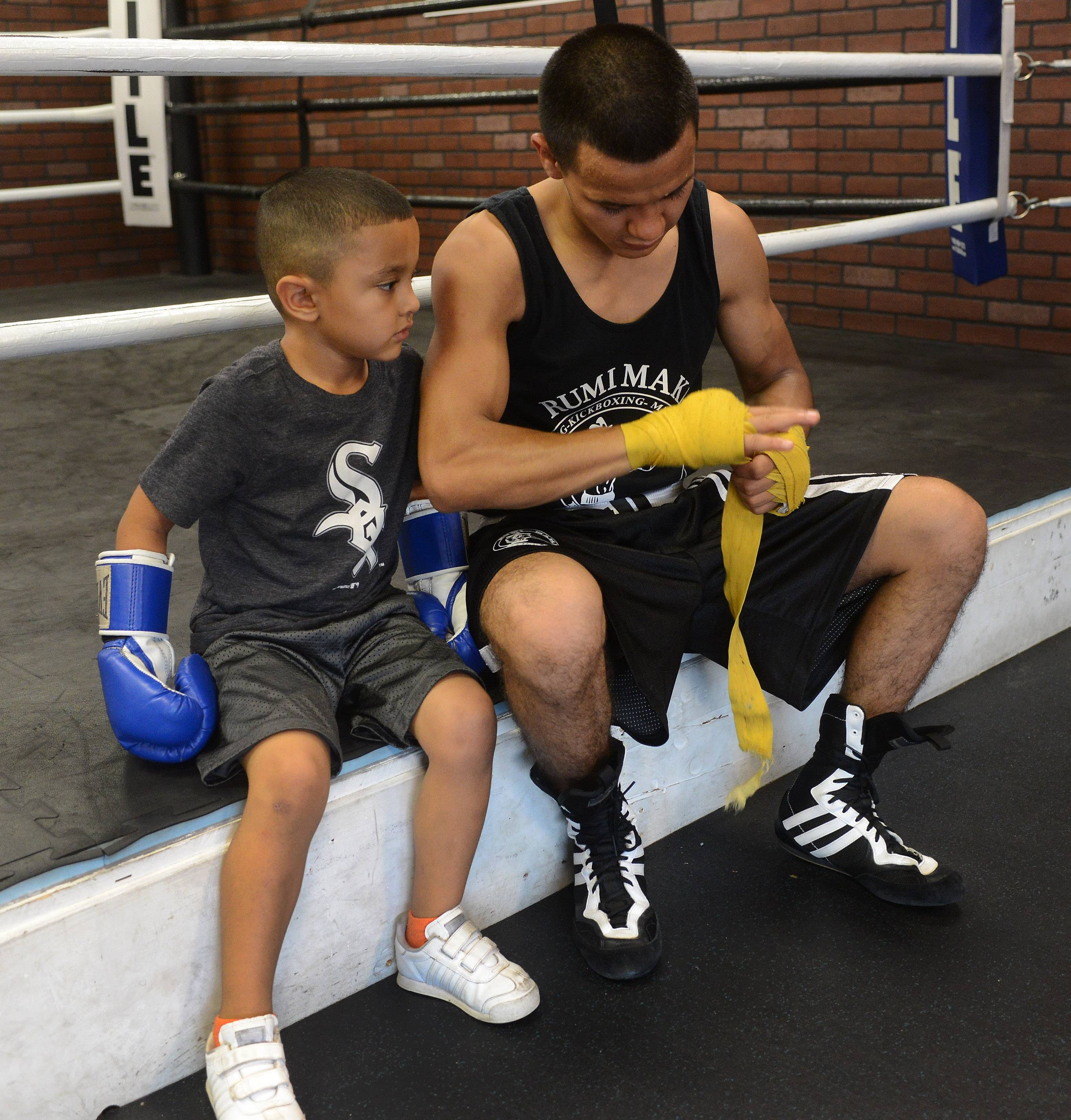 Javier Rivera, 19, of Palatine wraps his hands before a boxing workout as his nephew, Jose Angel Rivera, 4, watches.