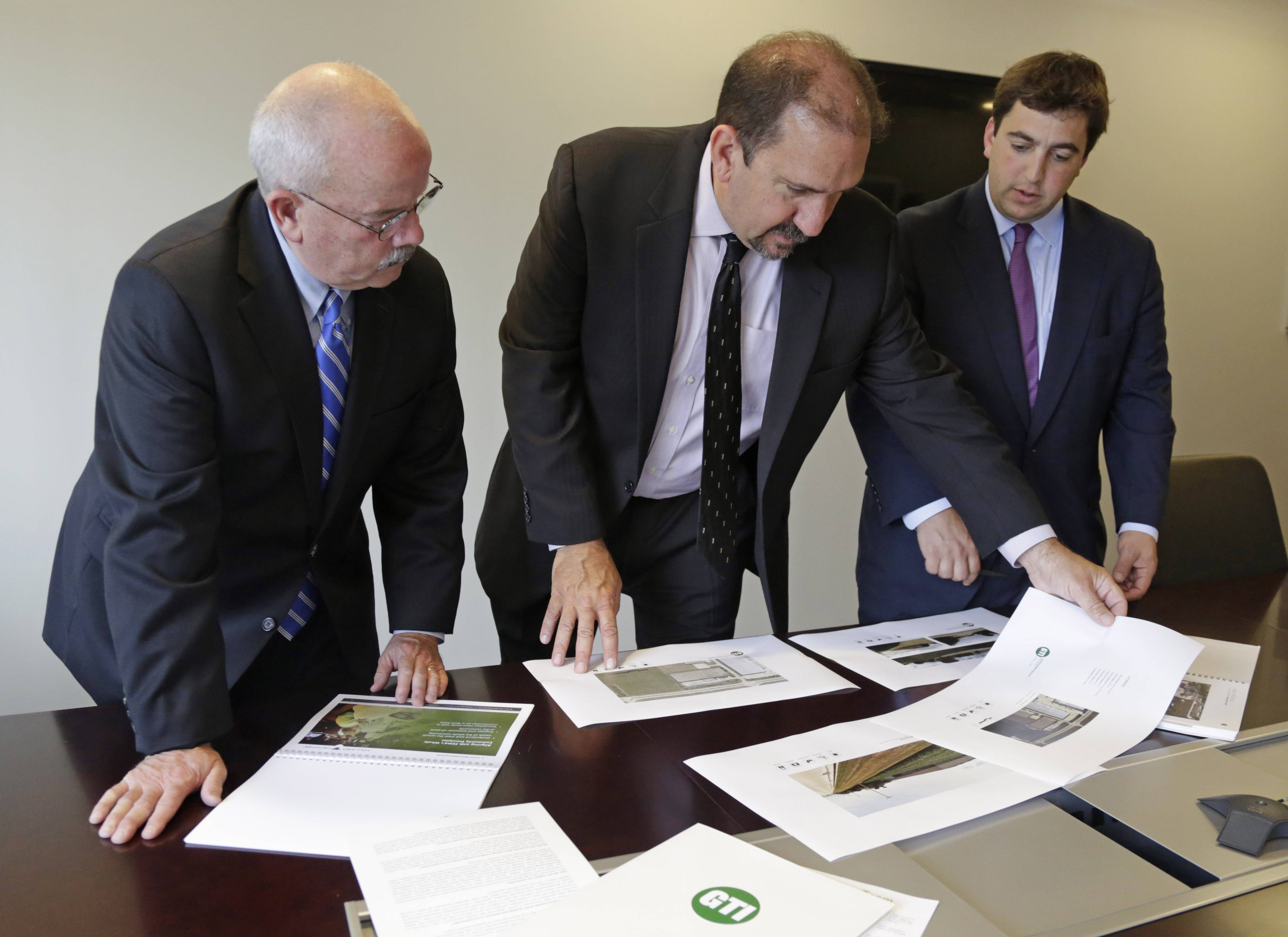 Kenneth Bouch, center, and Ben Kovler, right, of Green Thumb Industries, an Illinois-based partnership of medical marijuana entrepreneurs, review security plans for a proposed medical marijuana facility with security adviser Terry Gainer during a meeting Wednesday in Chicago.