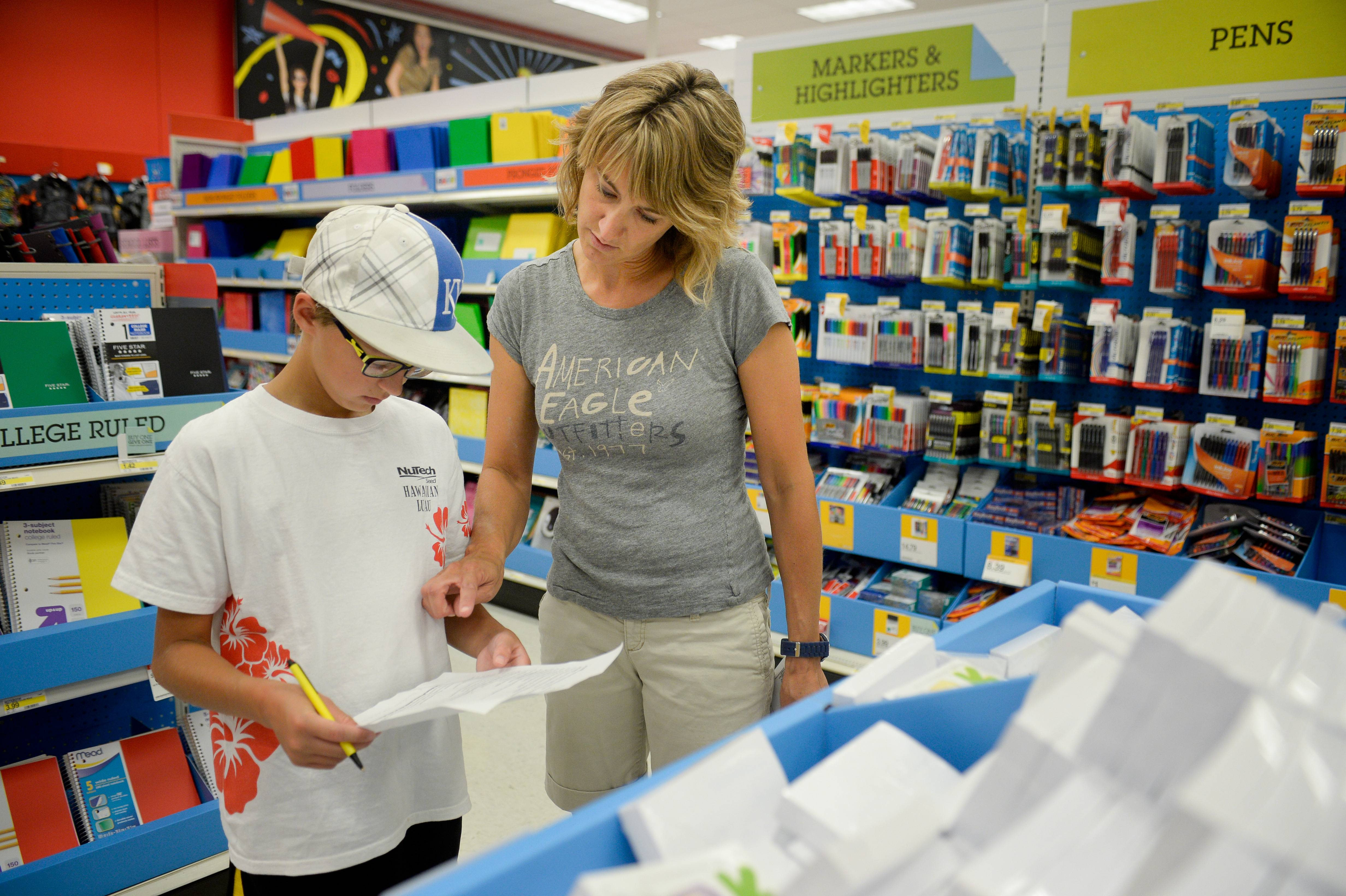 Jill Courtney, right, shops for school supplies for her sons, Will, left, and Reid, not seen, at a Target store in St. Joseph, Mo.