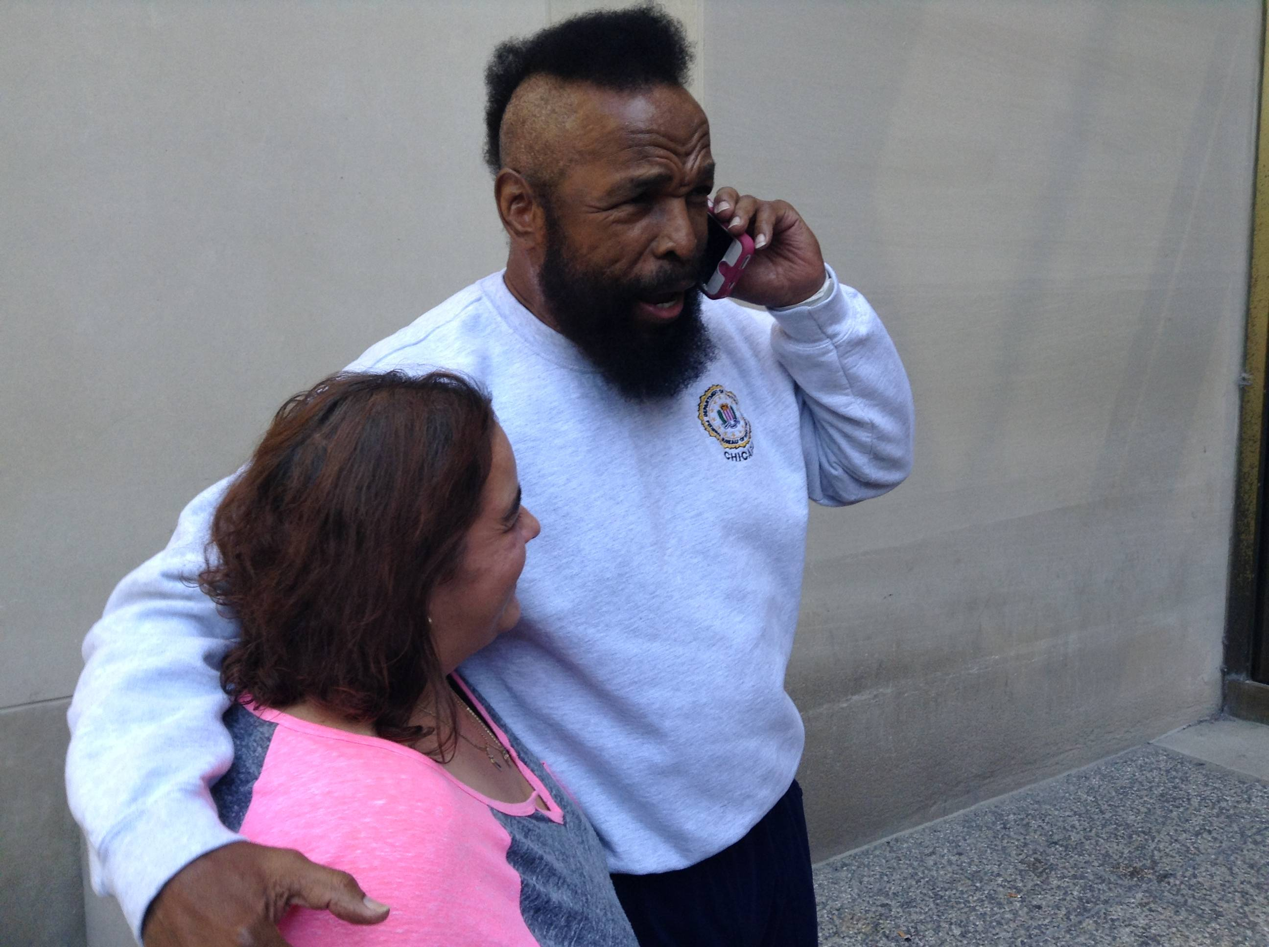 Mr. T poses with courthouse employee Yolanda Johnson of Lake in the Hills while he speaks to her mother on the phone. He was at the Rolling Meadows courthouse Friday for jury duty.