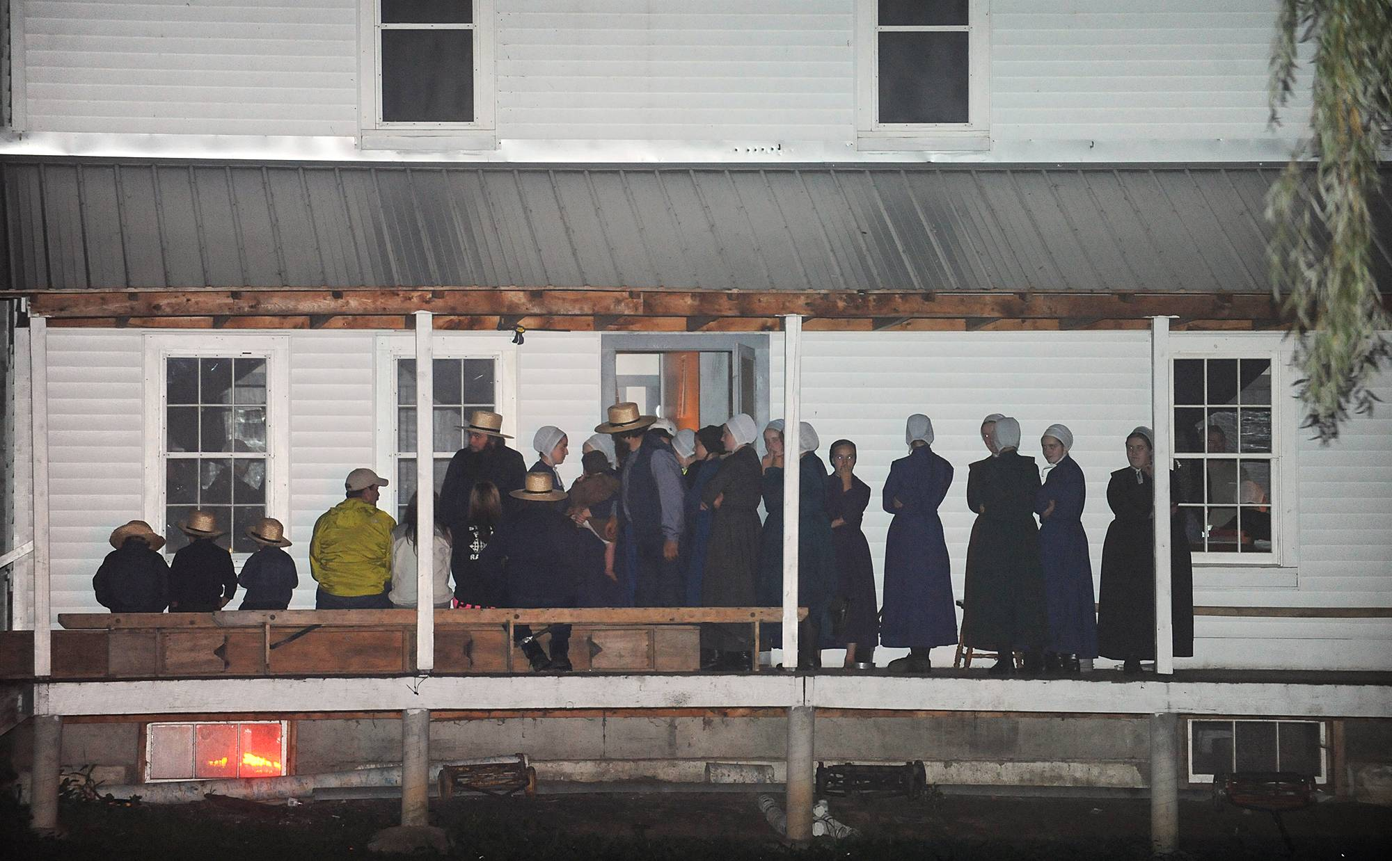 Supporters gather on the porch of a house at the intersection of Route 812 and Mt. Alone Road in Heuvelton, NY on Thursday, Aug. 14, 2014 after Fannie Miller, 12, and her sister Delila Miller, 6, were returned home safely after being abducted Wednesday night at a farm stand near their home.
