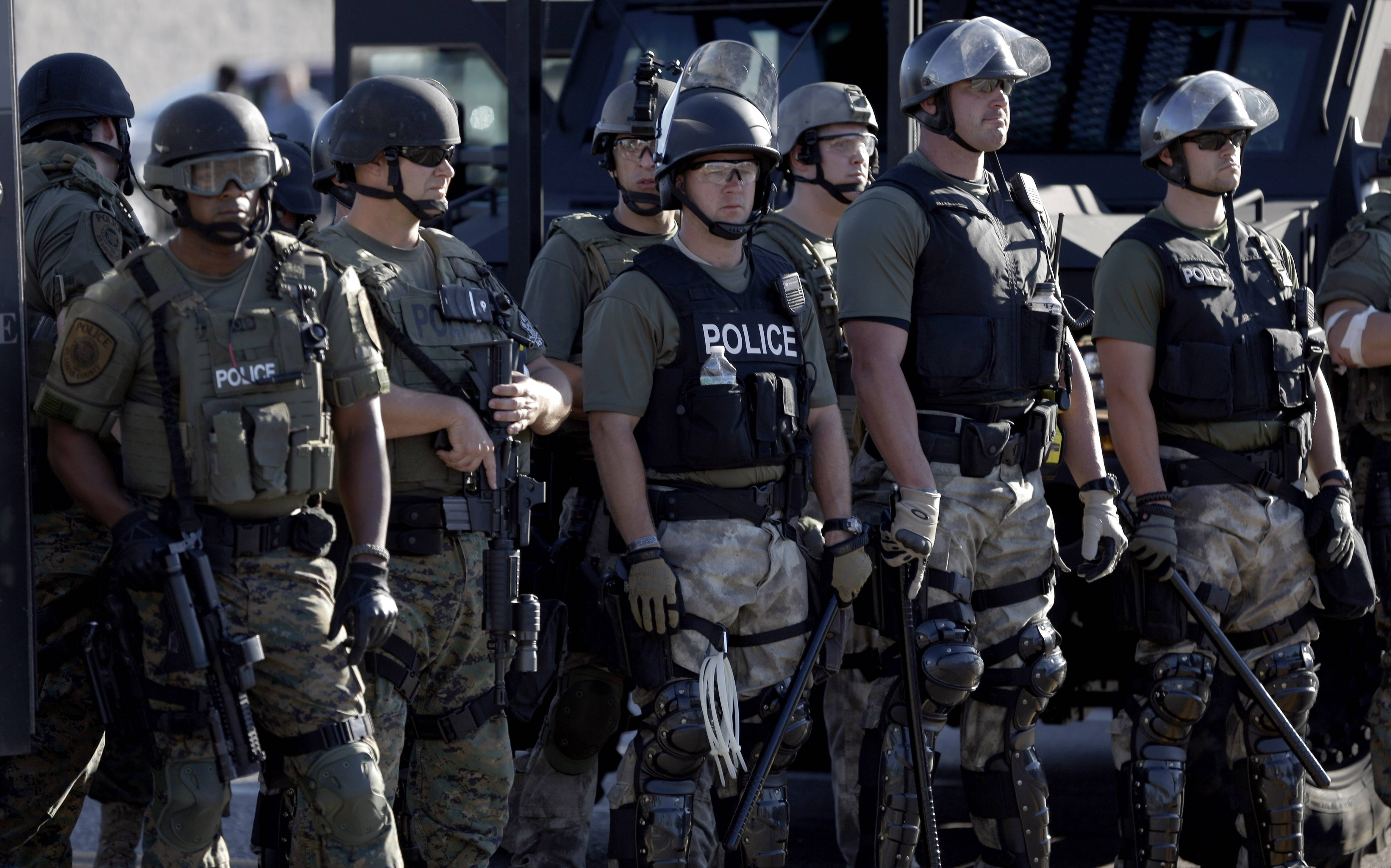 Images of police outfitted in paramilitary gear clashing with protesters in suburban St. Louis after the weekend shooting death of unarmed black teenager are giving new impetus to efforts to rein in a Pentagon program that provides free machine guns and other surplus military equipment to local law enforcement agencies.