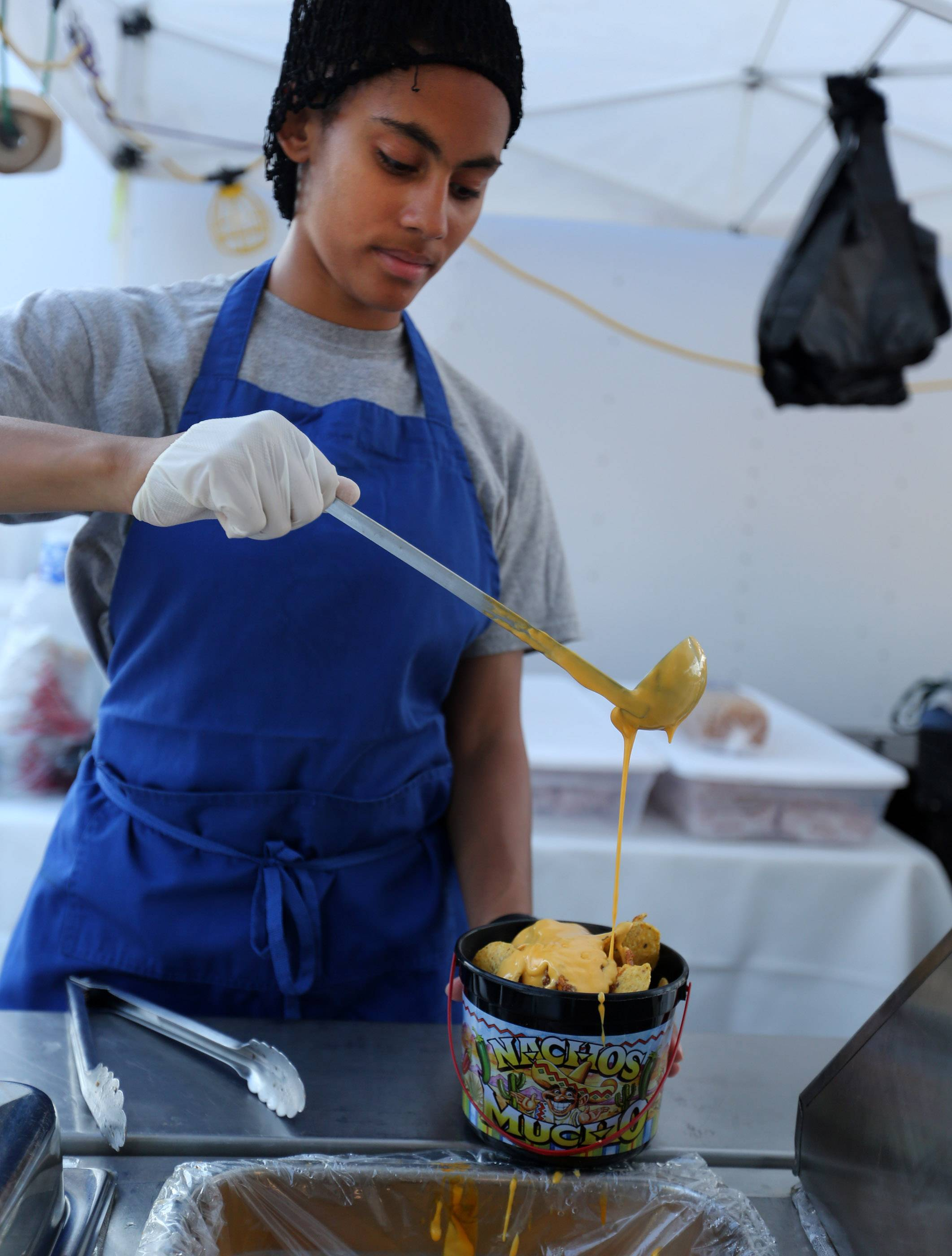 Paris Smith with the Brat Shop in Zion makes a taco bucket Friday at the Grayslake Summer Days festival
