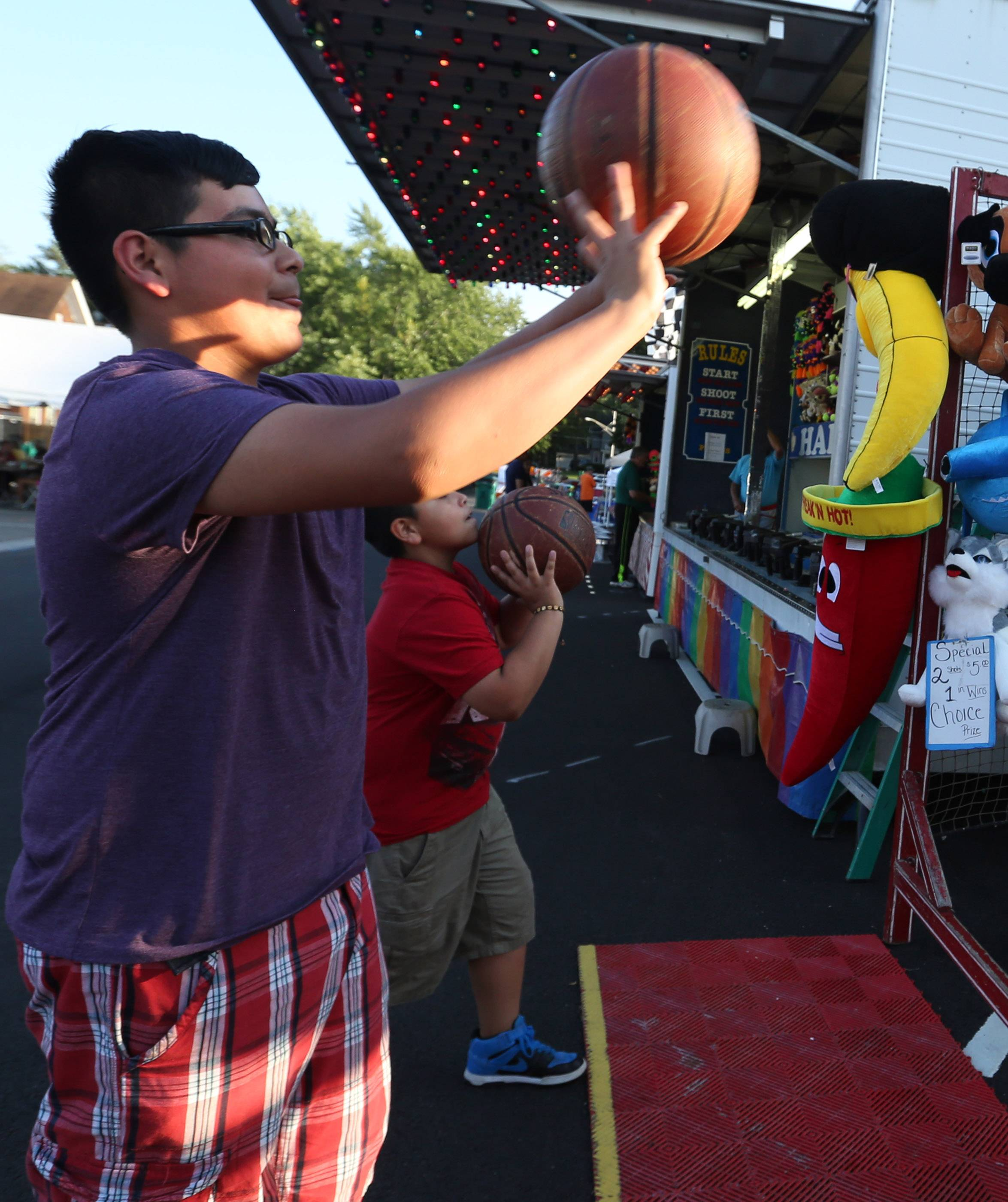 Chris Diaz, 12, and Alex Simon, 10, both of Round Lake Beach, take a shot at the basketball game Friday at the Grayslake Summer Days festival.