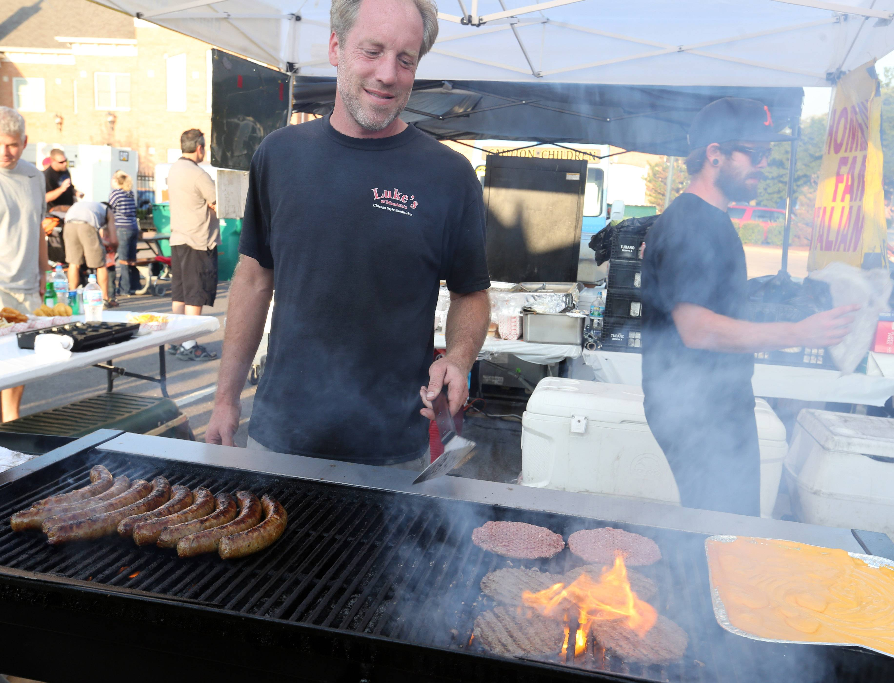 Mike Majestic, owner of Luke's of Mundelein, grills hamburgers Friday at the Grayslake Summer Days festival.