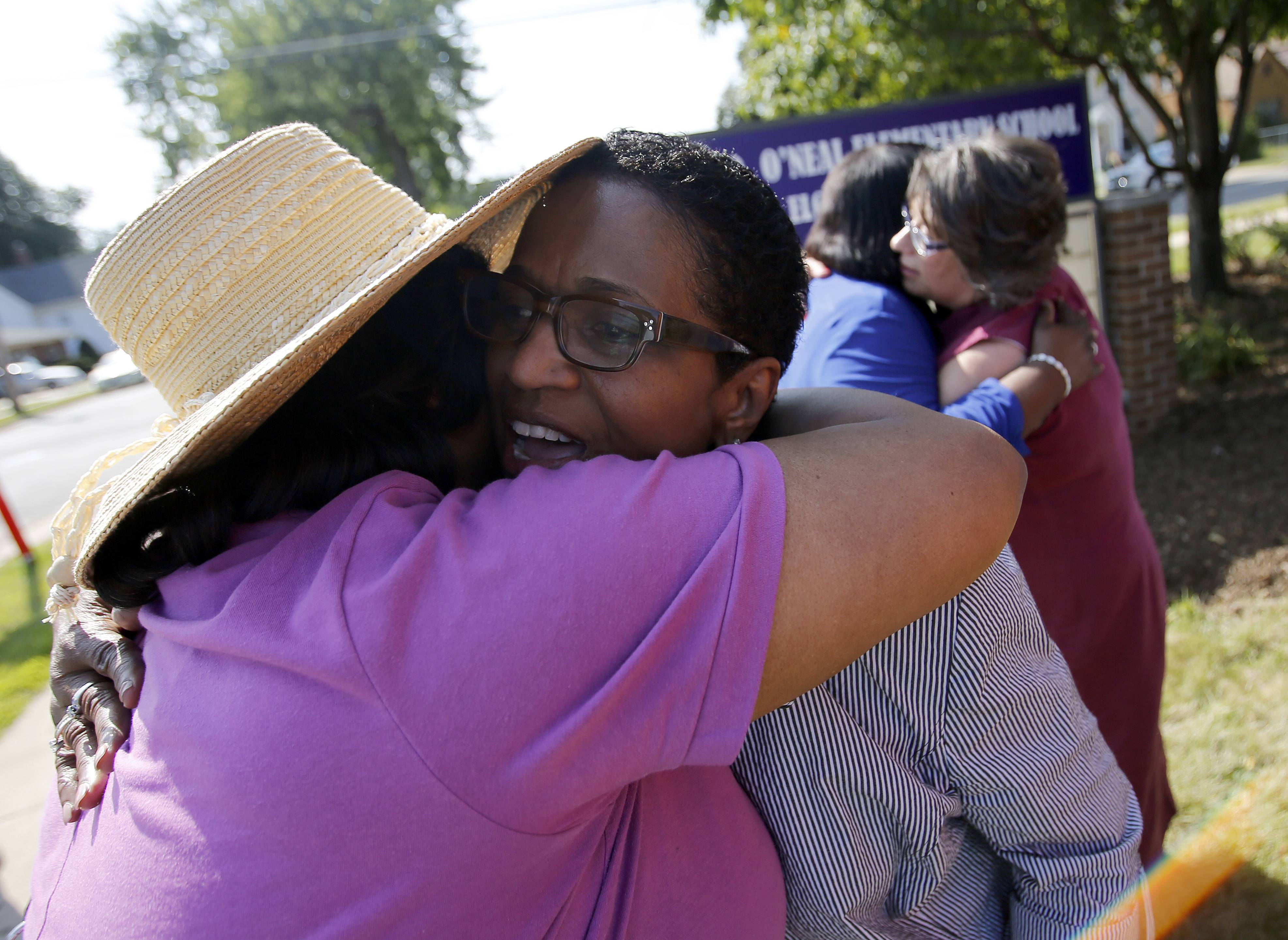 Carolyn O'Neal, wife of the late Ronald O'Neal, right, gets a hug from Delores Mayes-Howard after Sheridan Elementary School was renamed Ronald D. O'Neal Elementary School Friday in Elgin.
