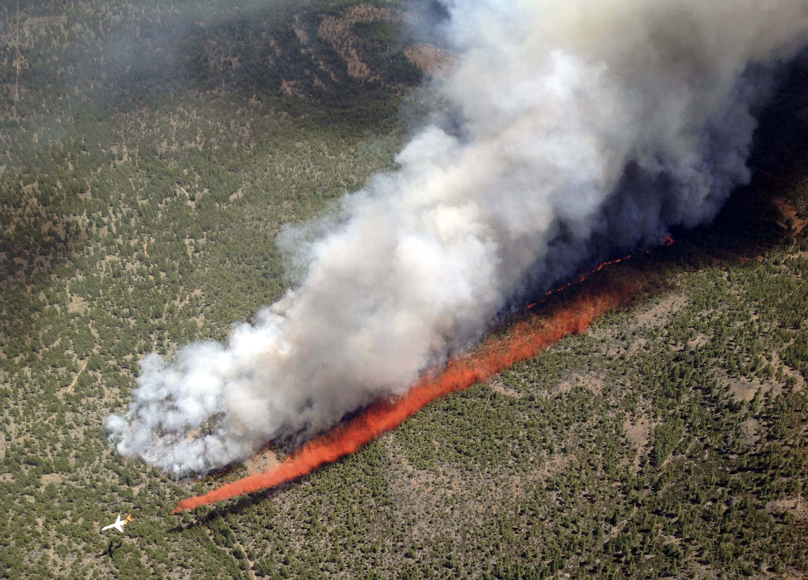 An MD-87 air tanker lays a line of retardant to flank the Two Bulls Fire burning at the Deschutes National Forest, about 10 miles west of Bend, Ore.
