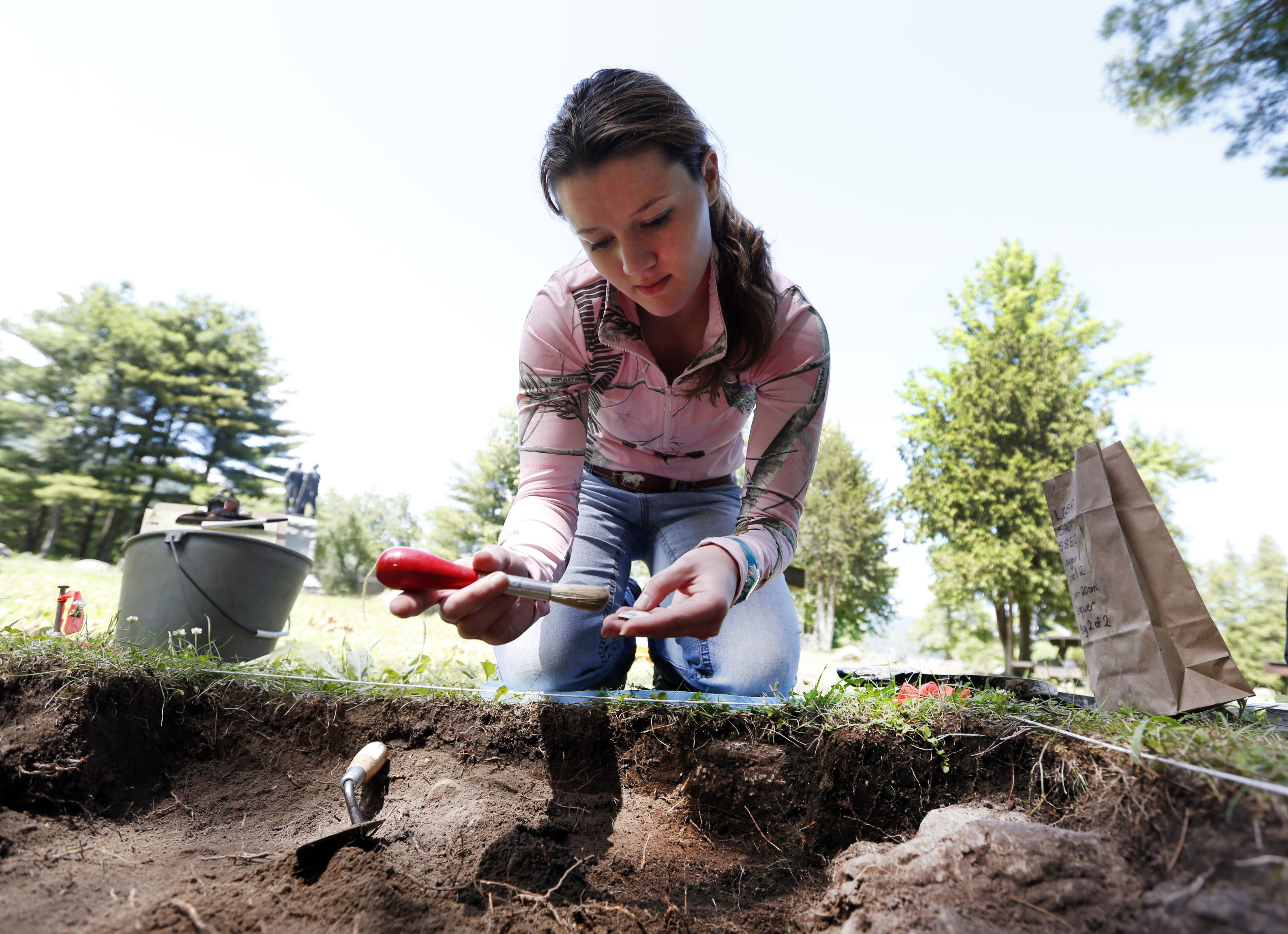 Volunteer Heather Engwer, of Lake George, N.Y., examines an artifact during an archaeological field school dig at Lake George Battlefield Park in Lake George, N.Y.