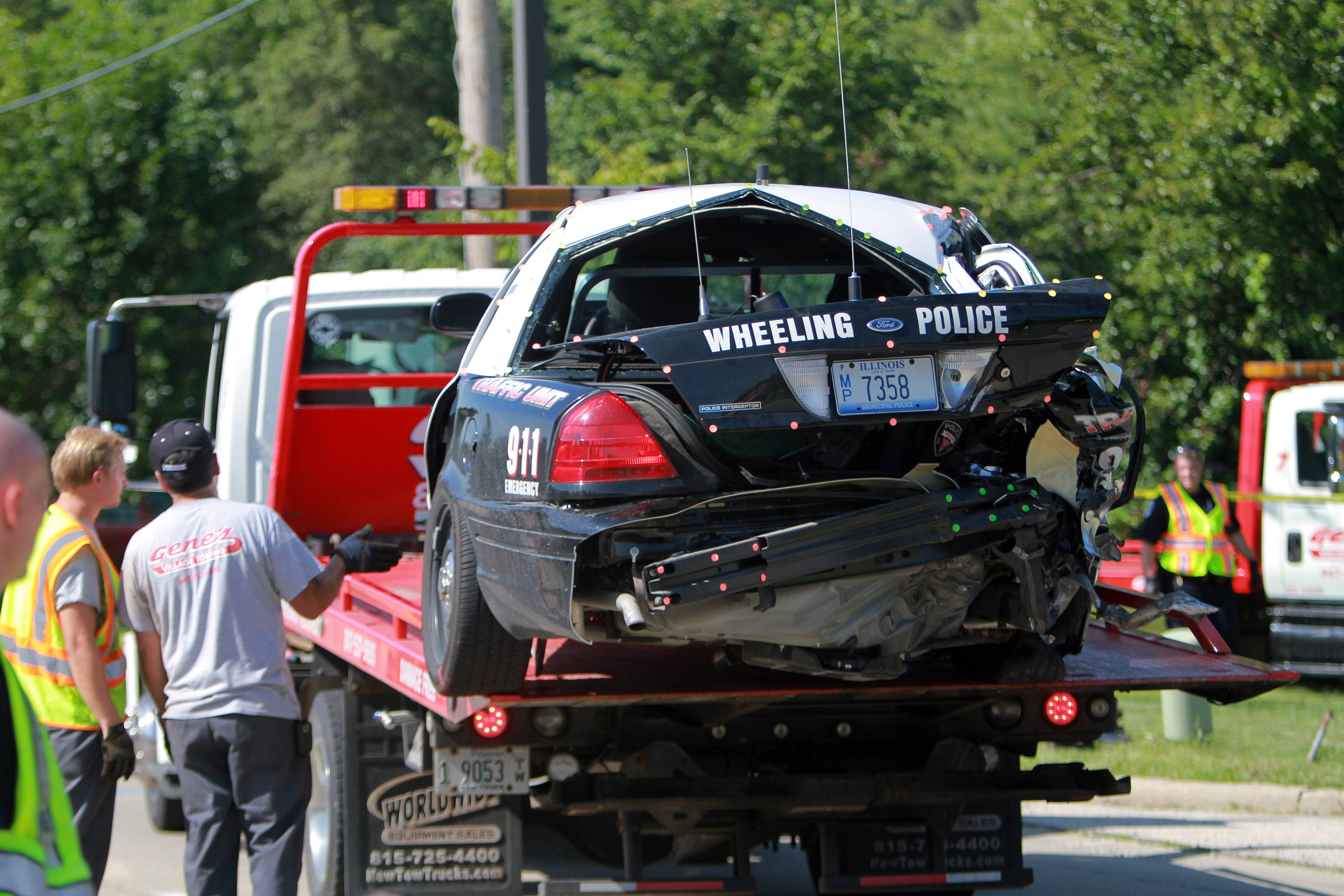 The Wheeling police car is loaded onto the tow truck after a car rear-ended a it on Milwaukee Avenue just north of Hintz Road in Wheeling.
