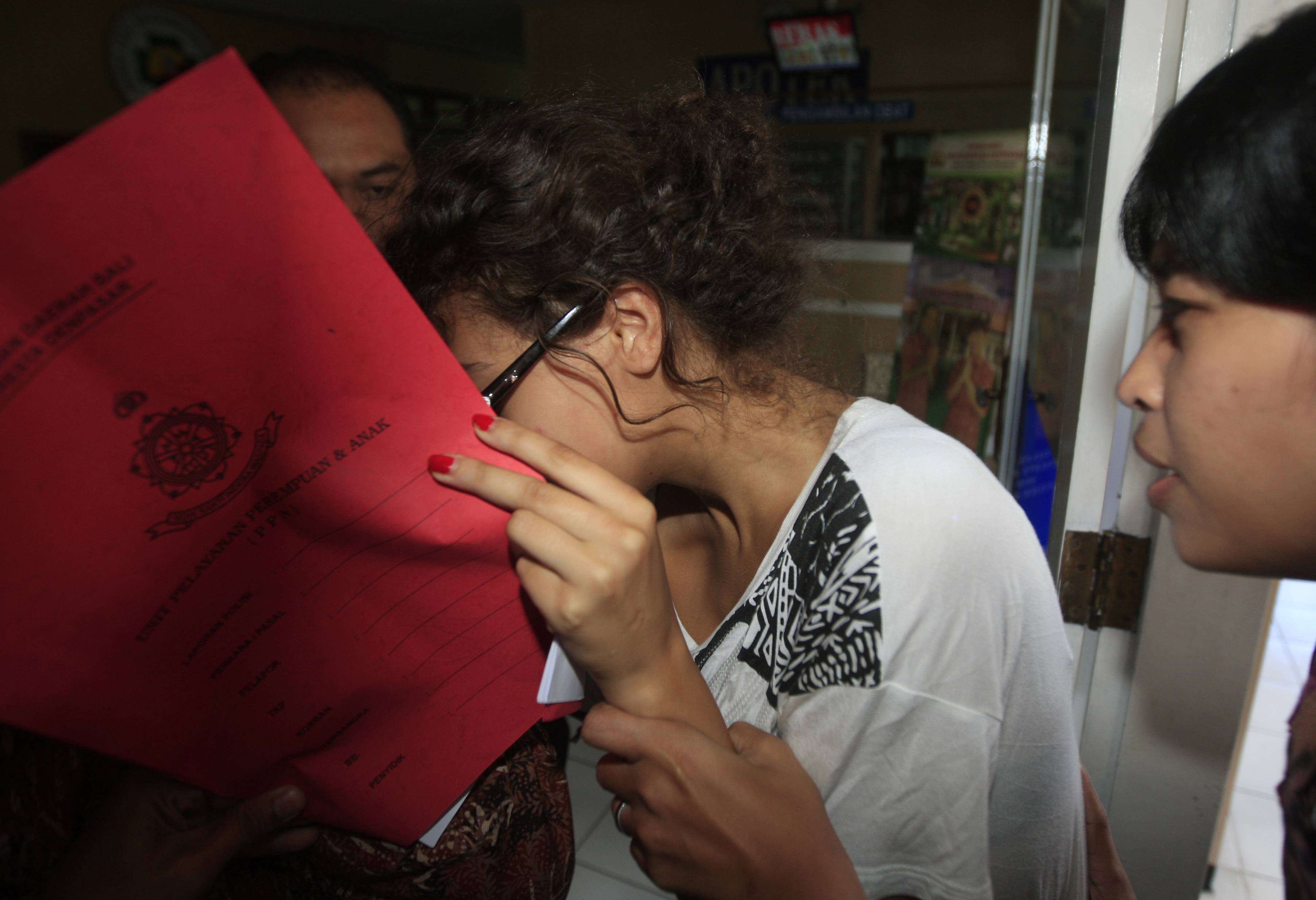 Heather Mack, covering her face, is led to a hospital Friday for a medical check by Indonesian police officers. Mack has been charged in the death of her mother, Sheila von Wiese-Mack, in Bali, Indonesia.
