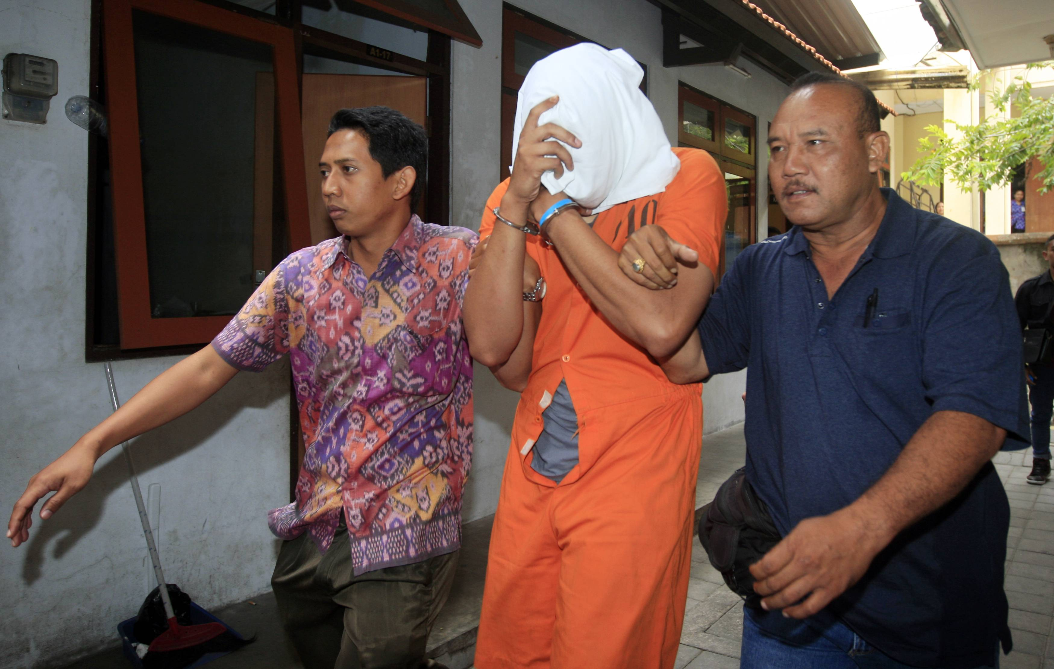 Indonesian police officers escort murder suspect Tommy Schaefer, covering his face, to a hospital for medical check Friday in Bali.