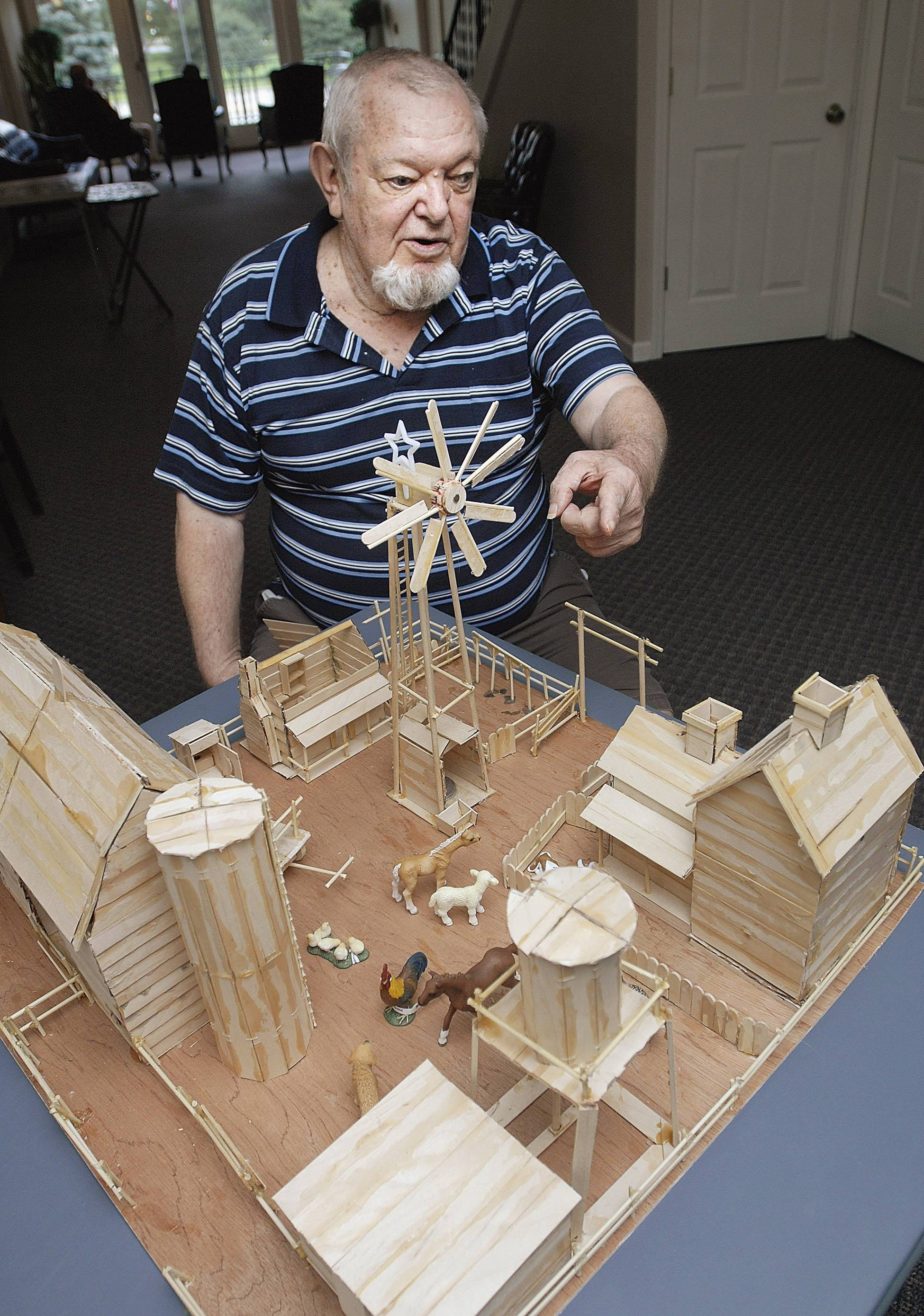 Hock sits with a 4-foot square farmstead he made completely out of tongue depressors, popsicle sticks and other various wood products at The Myerling, an assisted living group home.