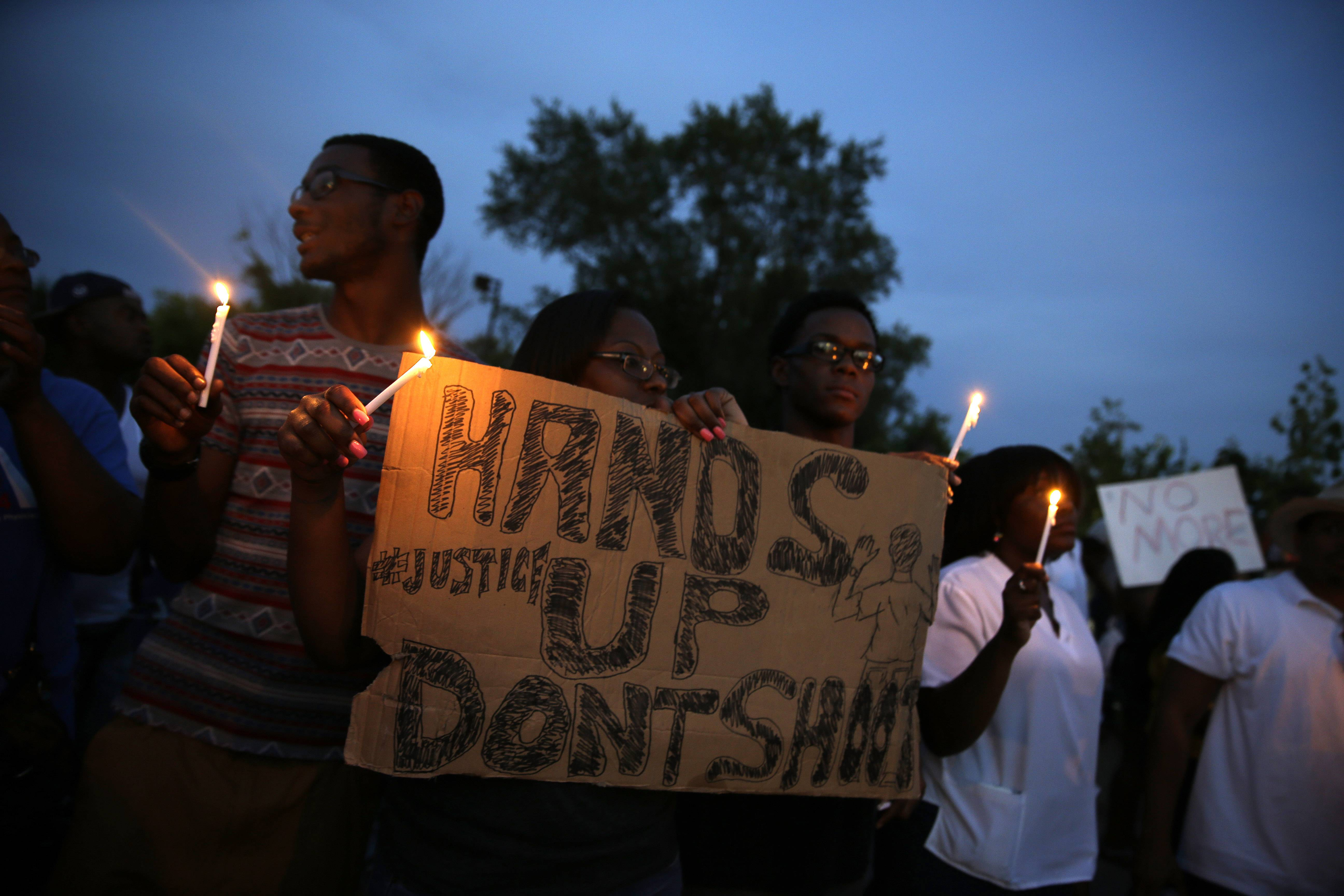 Demonstrators hold candles and signs Thursday, Aug. 14, 2014, in Ferguson, Mo. Hundreds of people protesting the death of Michael Brown marched through the streets of Ferguson alongside state troopers Thursday.