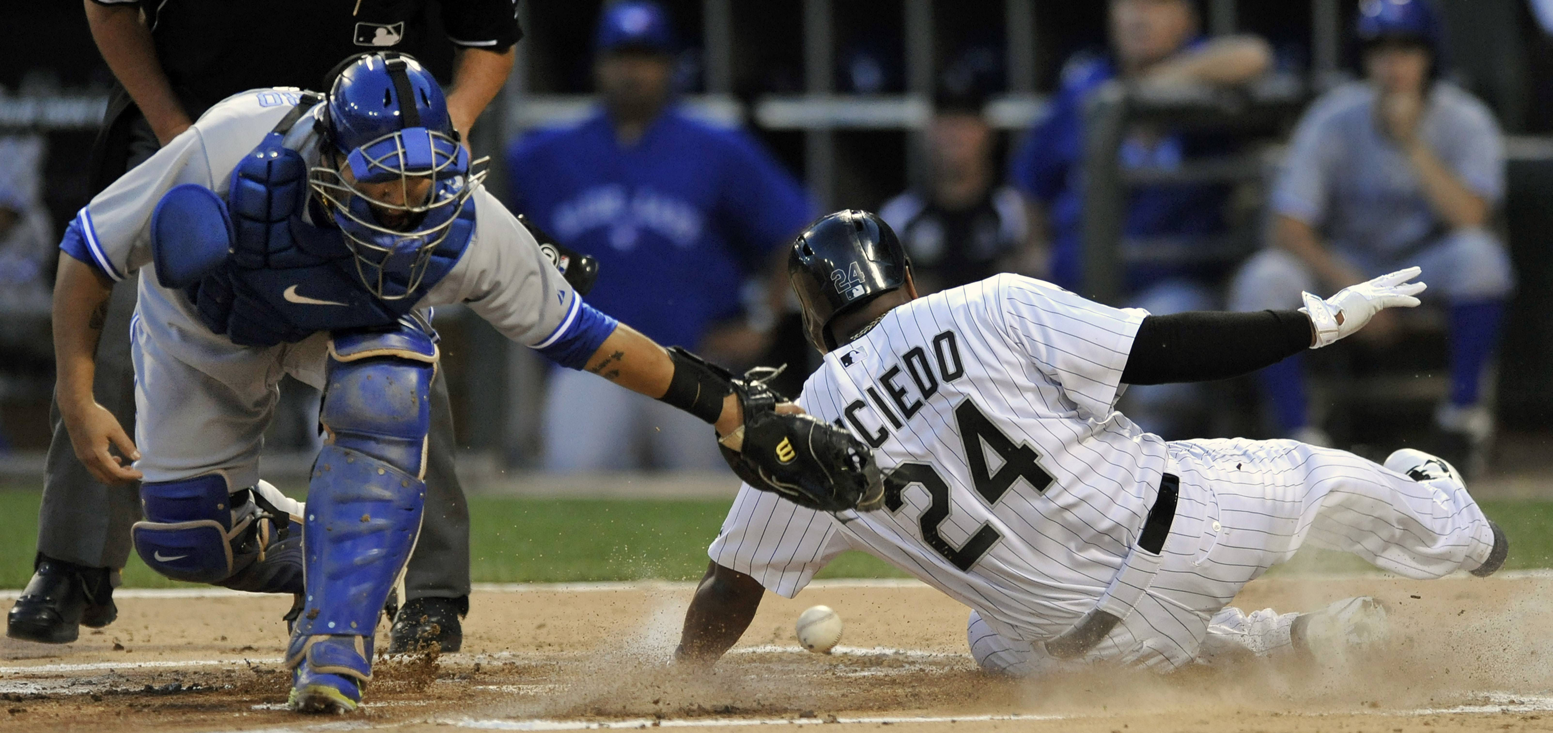 Dayan Viciedo of the White Sox scores in the first inning as Toronto Blue Jays' catcher Dioner Navarro is late trying to apply the tag in Friday's contest.