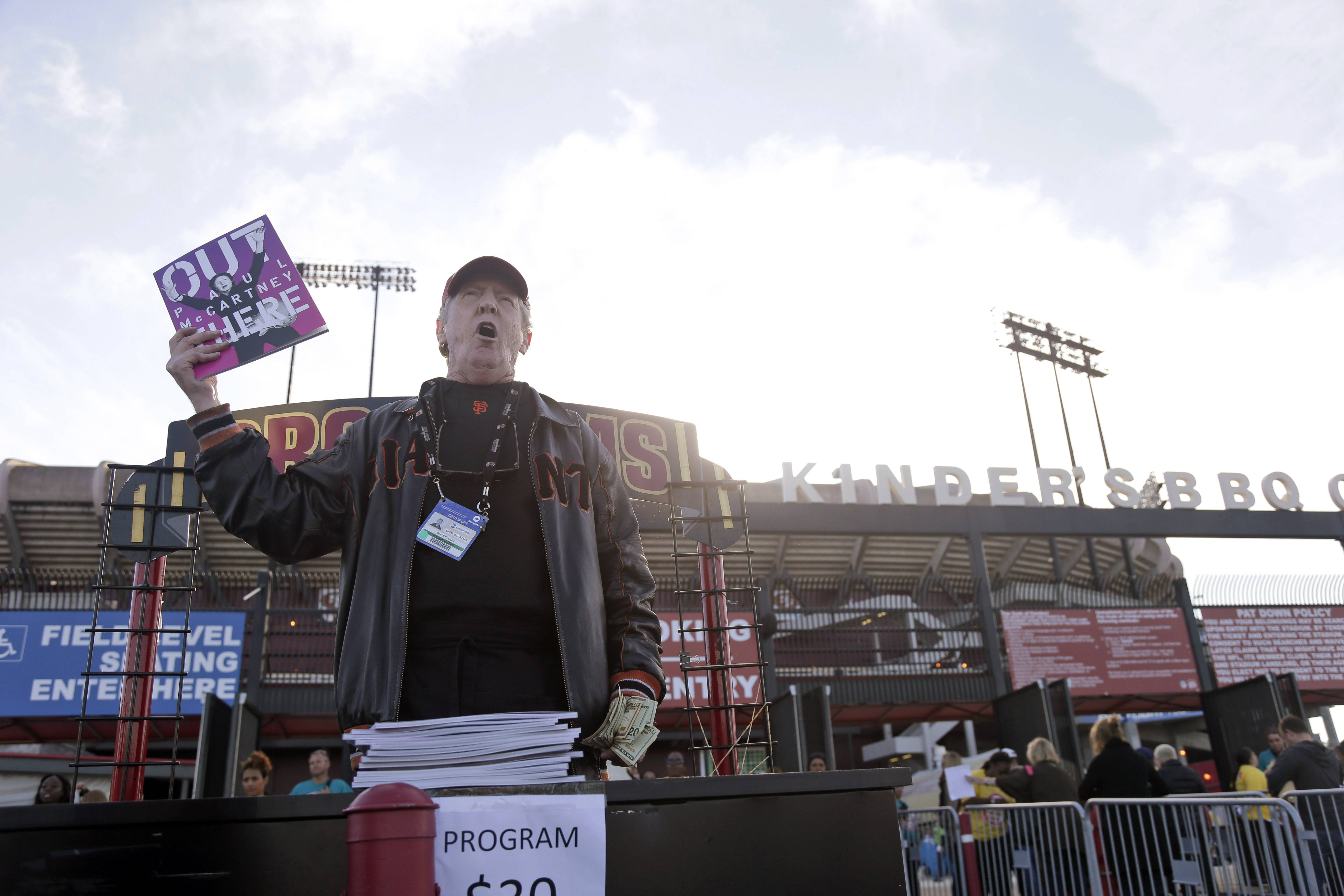 A program vendor stands outside Candlestick Park before a Paul McCartney concert Thursday, Aug. 14, 2014, in San Francisco. San Francisco is saying goodbye to the stadium where its beloved Giants and 49ers celebrated some of their greatest triumphs.