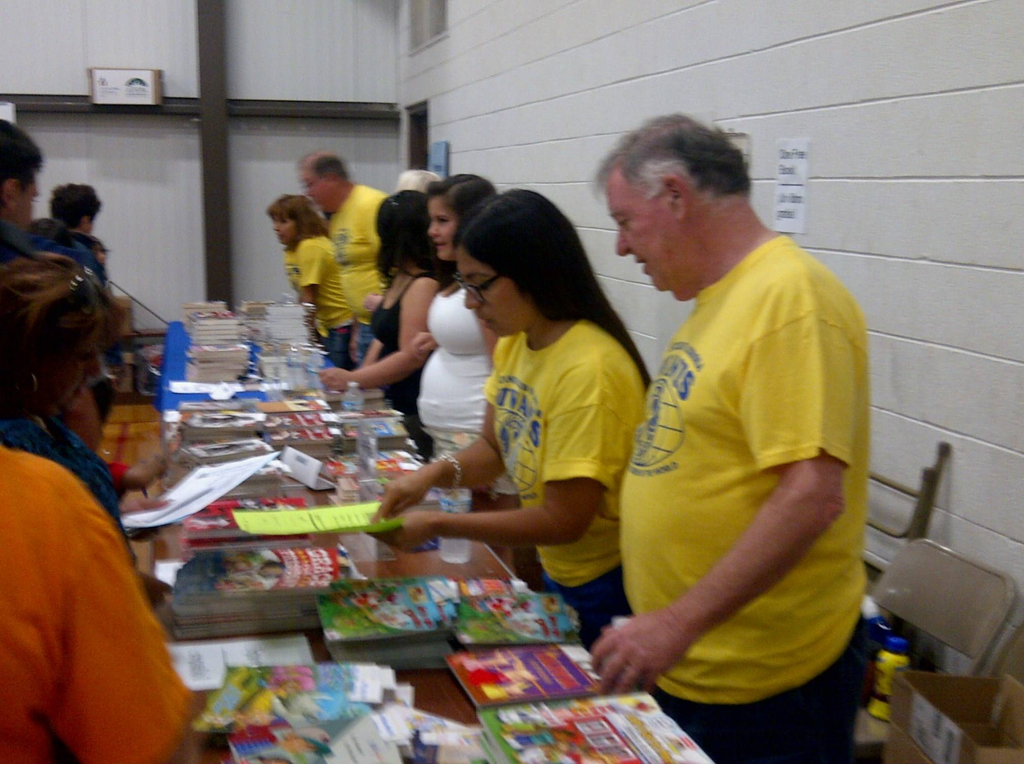 Kiwanis Club of Aurora members Father Ray Diesbourg and Christina Campos help distribute free children's books at Aurora's annual Project Unity/Communities in Schools Back-to-School Fair on Aug. 9.