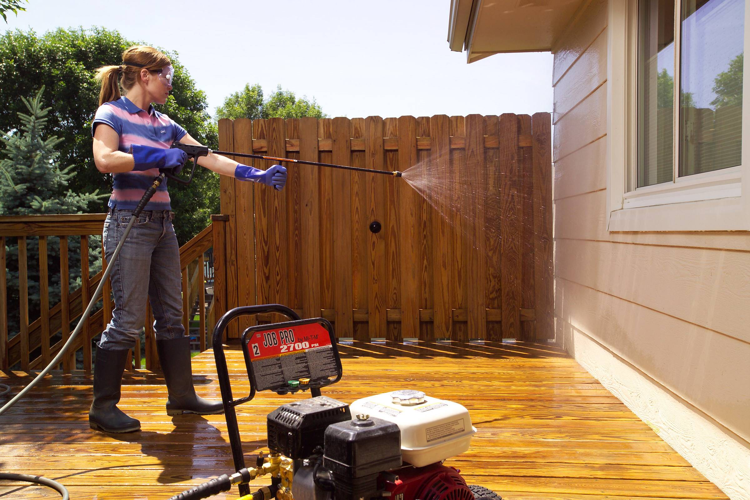 In addition to wooden decks, spray from a power washer can be used to clean and rinse siding and the windows of a house. Use a low pressure to avoid damage.