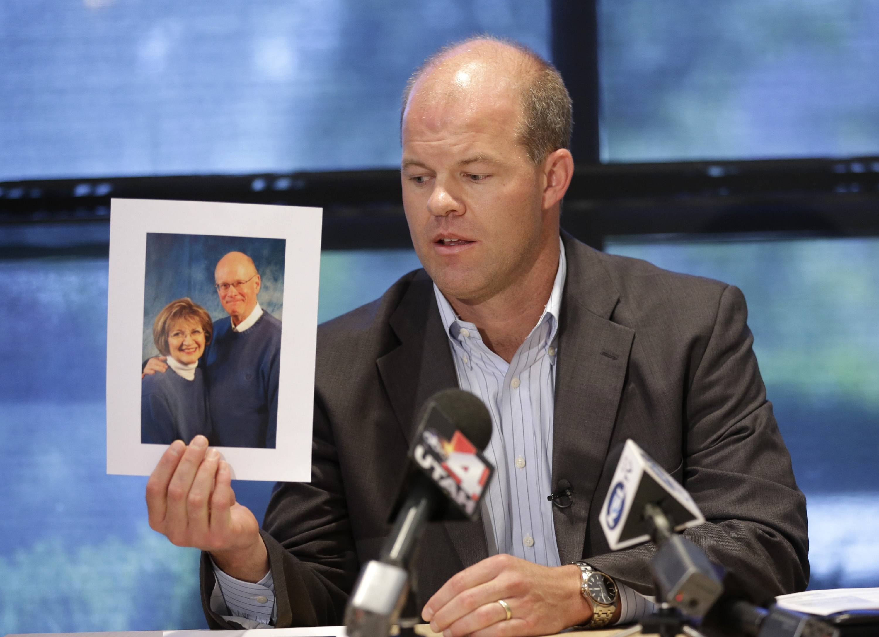 Attorney Paxton Guymon holds a photograph of Jim and Jan Harding during a news conference Thursday in Salt Lake City.