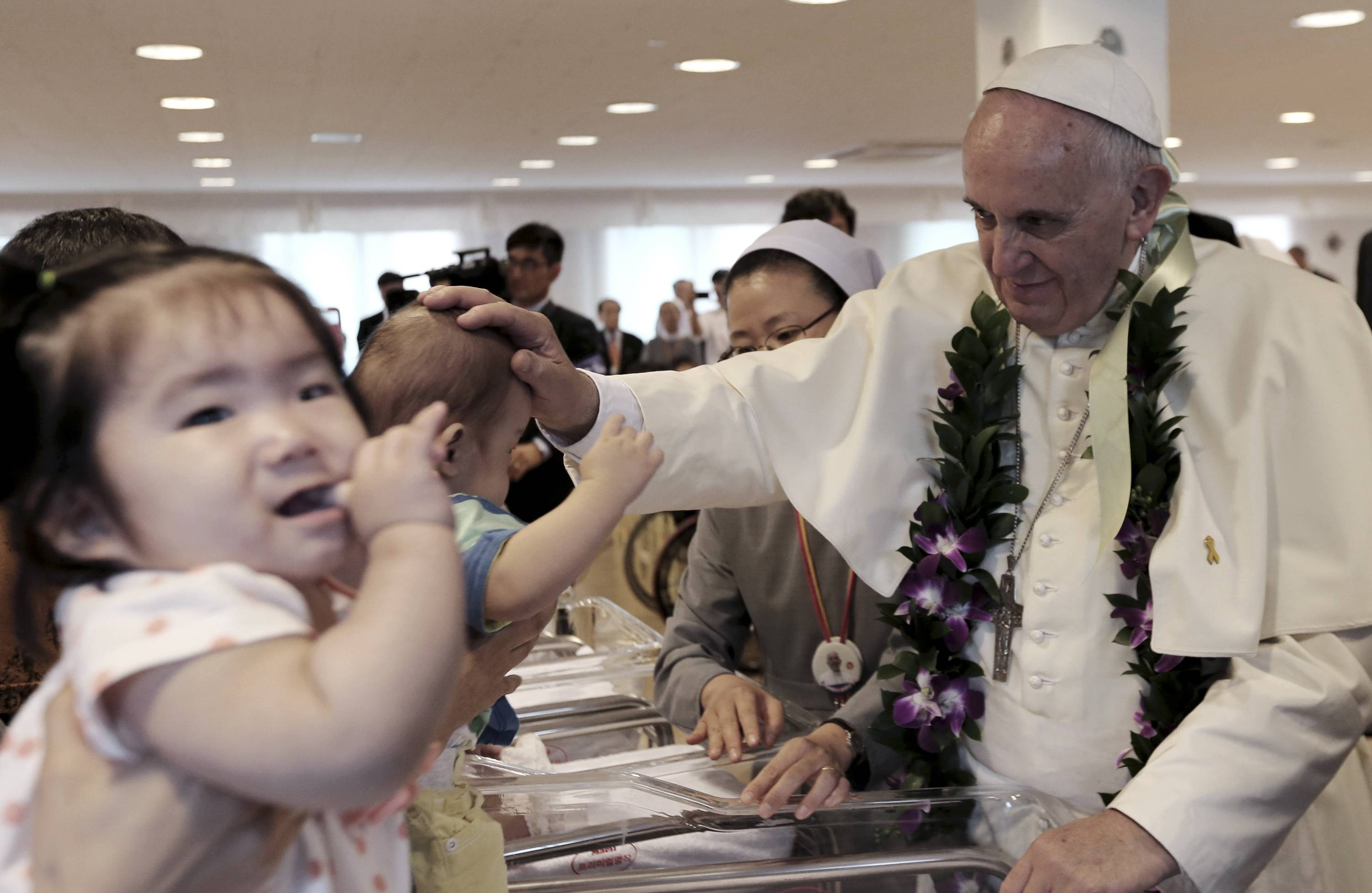 Pope Francis blesses a child who is planned to be adopted by a family, during his visit to the rehabilitation center for disabled people at Kkottongnae in Eumseong, South Korea, Saturday, Aug. 16.