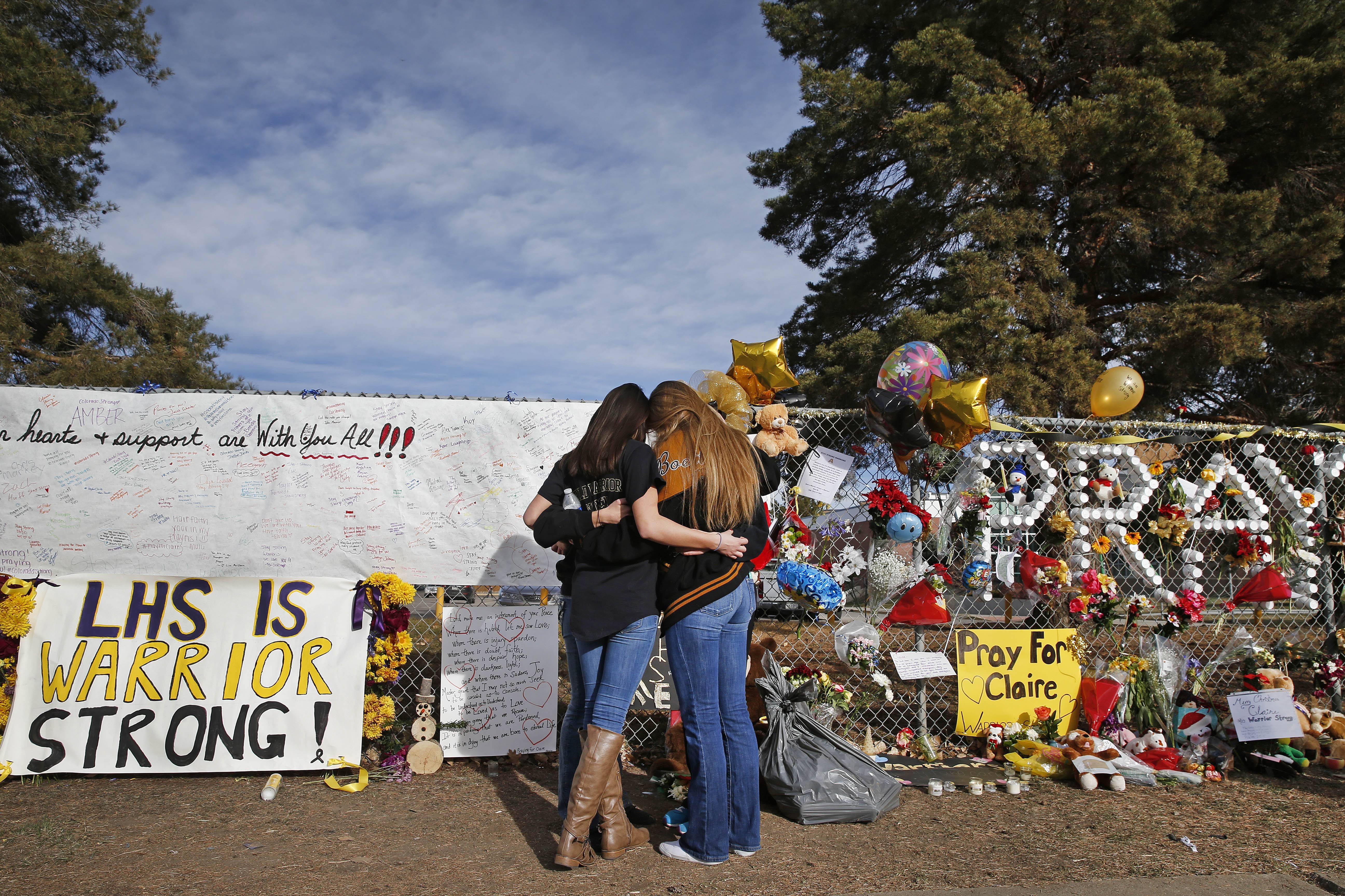 "In this December 2013 file photo, Arapahoe High School students hug at a tribute site for fatally-wounded student Claire Davis, who was shot by classmate Karl Pierson during a school attack six days earlier at Arapahoe High School, in Centennial, Colo. School disciplinary documents obtained Associated Press show that less than a week after Pierson shouted a death threat against his debate coach in a school parking lot, school officials determined that he was ""not a high-level of threat"" and allowed him to return to his classes."