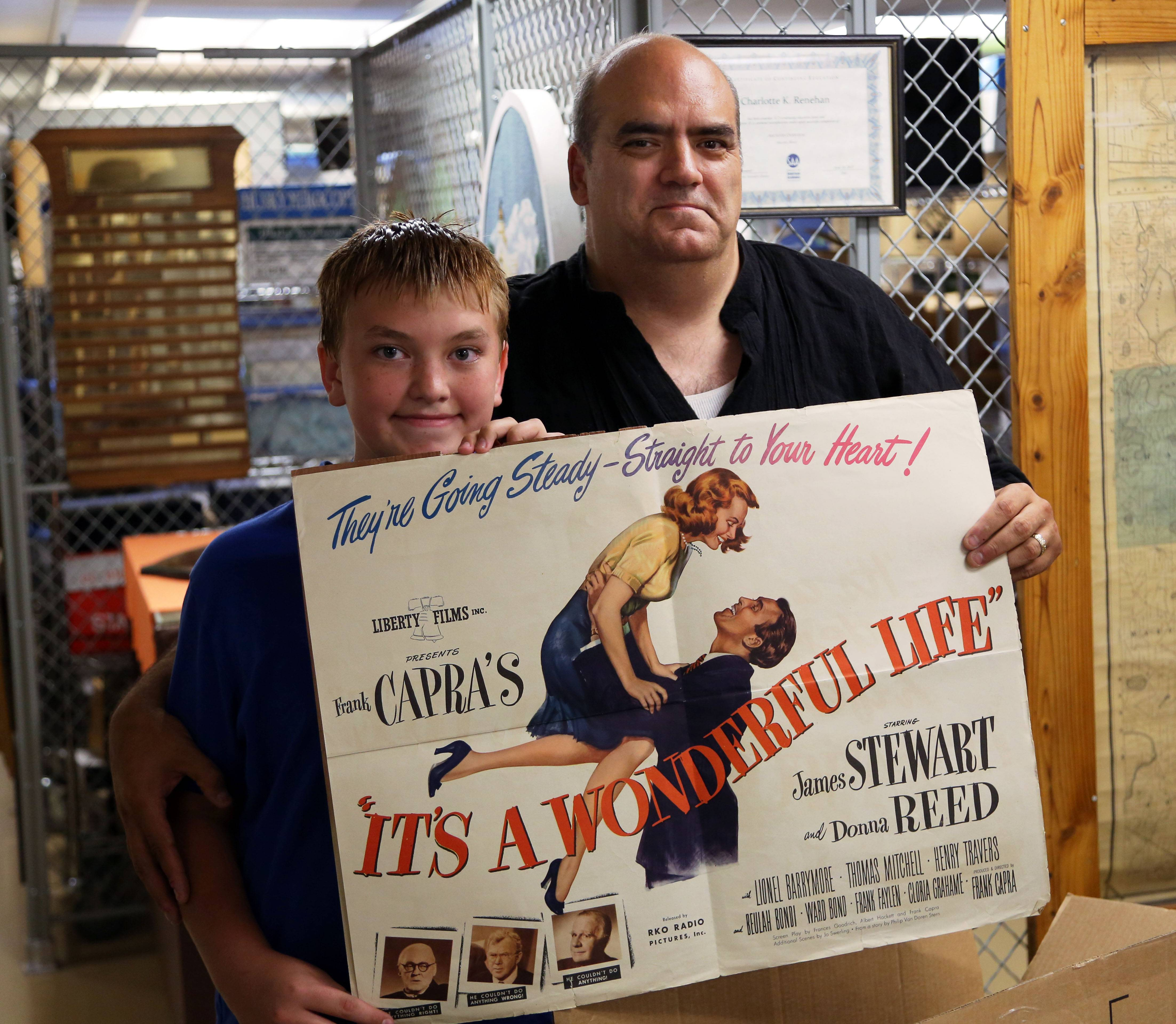 "Richard Goodson, right, and his 12-year-old son, Matthew, hold a promotional poster from ""It's a Wonderful Life."" Goodson says he enjoys sharing his vast collection related to the 1946 movie."