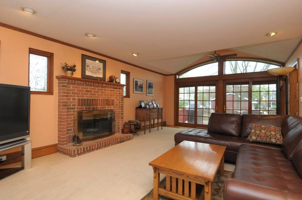 The family room features a wood-burning fireplace and large arched window.