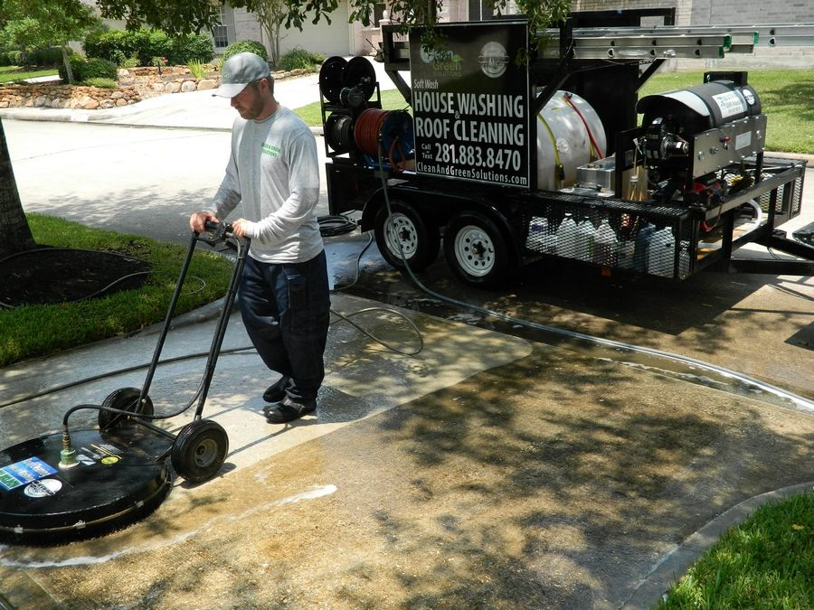 Joshua Harris of Clean and Green Solutions uses a cleaning solution and power-washing scrubber, shown here, to clean grime off concrete.