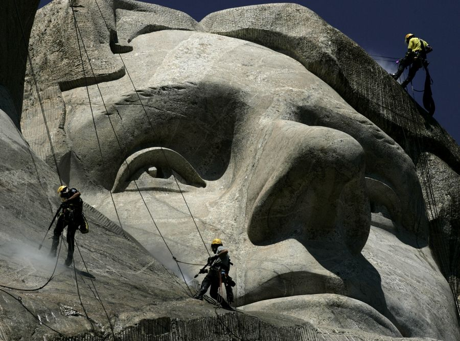 German workers Gerhard Buchar, right, and Winfried Hagenau, left, along with National Park Service employee Darin Oestman use pressure washers in 2005 to clean around the face of Thomas Jefferson at Mount Rushmore National Memorial in South Dakota. The granite sculptures hadn't been washed since they were completed 65 years ago by sculptor Gutzon Borglum.