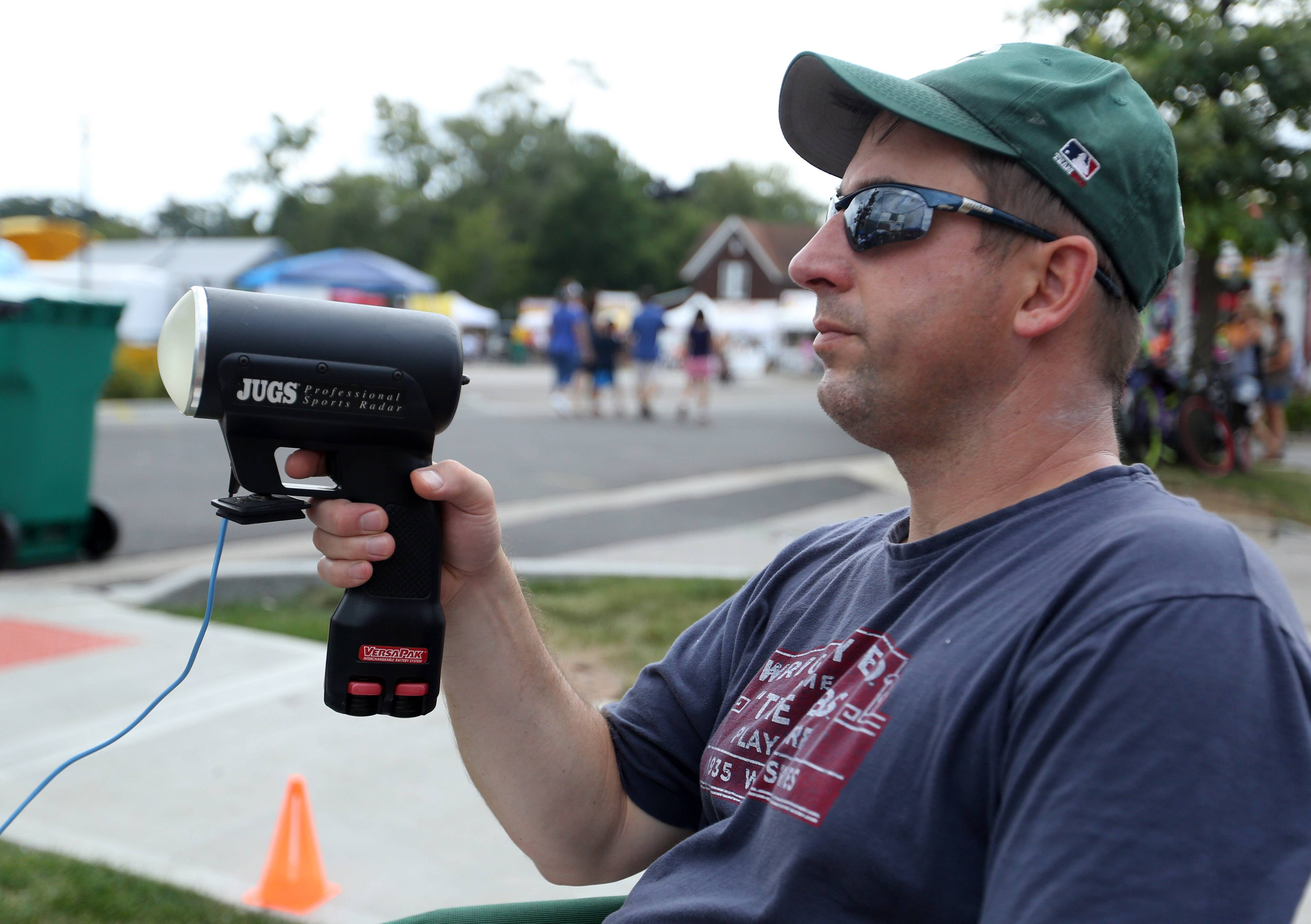 Jim Chamernik, a coach with Grayslake Youth Baseball Association, times a pitch using a radar gun at the association's pitching booth on Saturday during the second day of the Grayslake Summer Days festival in downtown.
