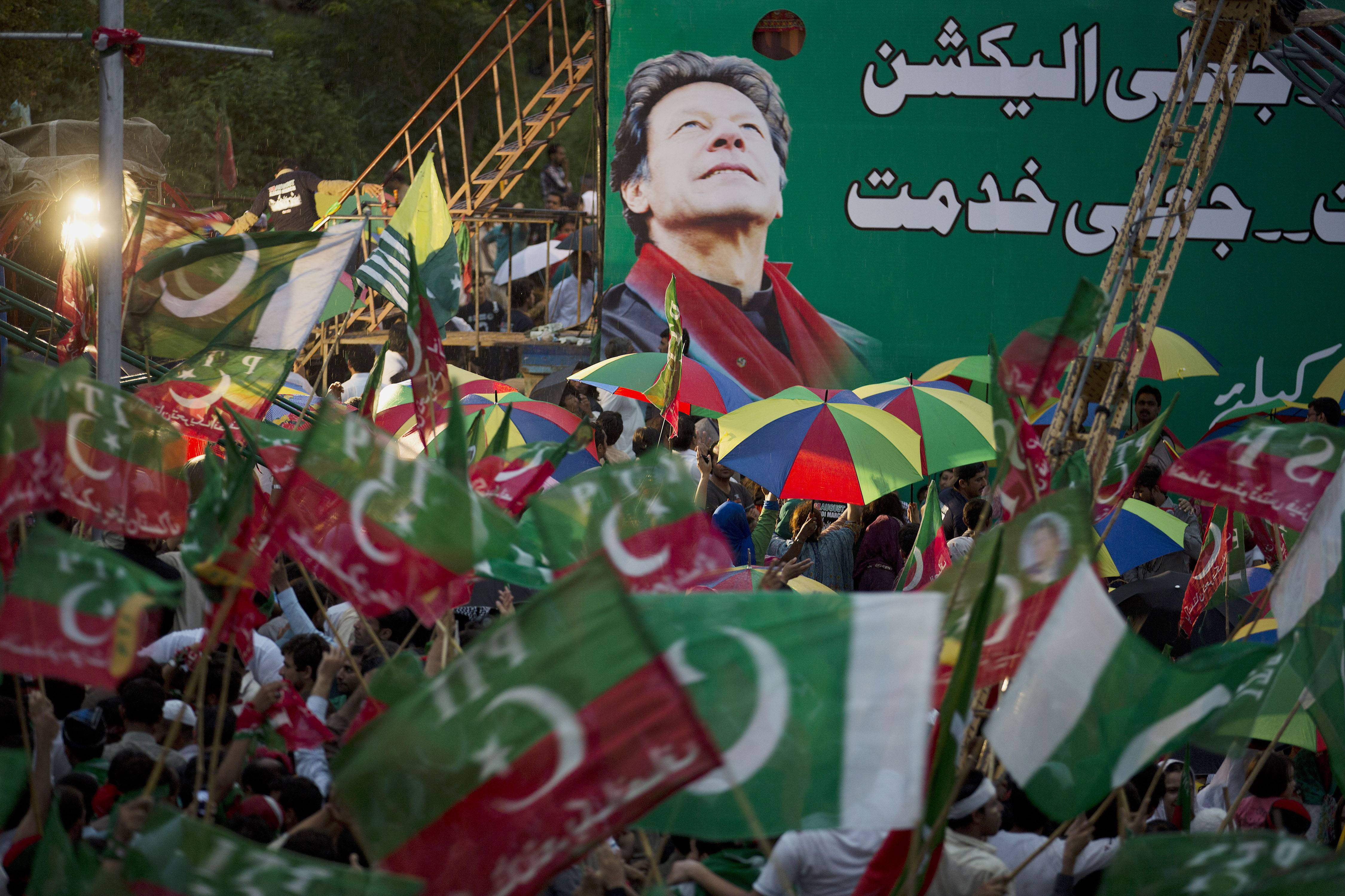 Supporters of Pakistan's cricketer-turned-politician Imran Khan wave their party flags Saturday at a rally in Islamabad, Pakistan.